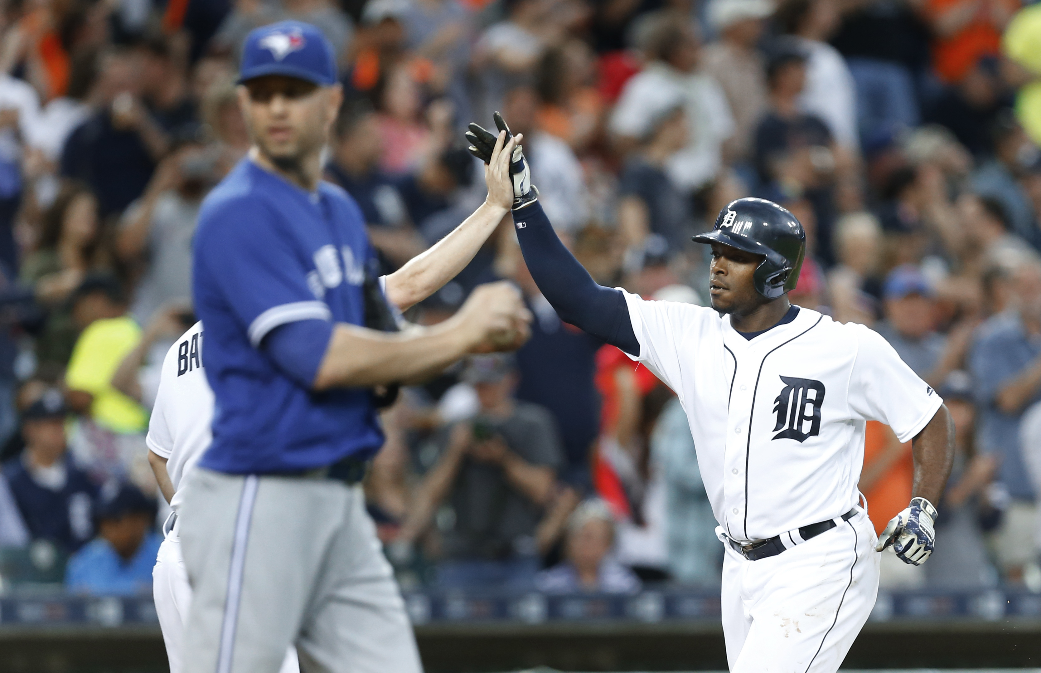 Detroit Tigers' Justin Upton, right, celebrates his two-run home run as Toronto Blue Jays pitcher J.A. Happ walks back to the mound in the third inning of a baseball game, Monday, June 6, 2016 in Detroit. (AP Photo/Paul Sancya)