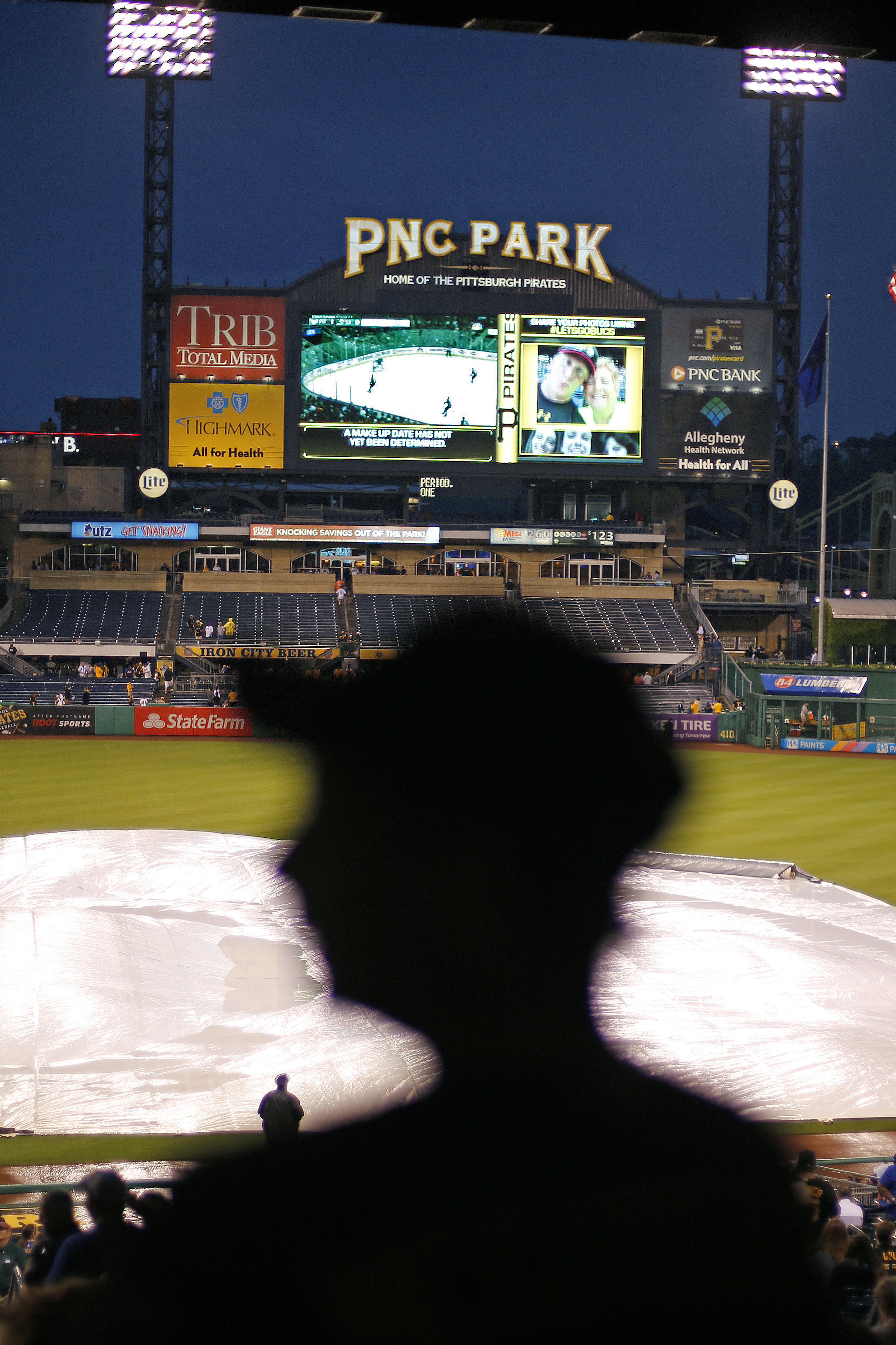 Baseball fans watch Game 4 of the Stanley Cup Finals series between the Pittsburgh Penguins and San Jose Sharks on the scoreboard at PNC Park before the baseball game between the Pittsburgh Pirates and the New York Mets was postponed due to rain in Pittsb