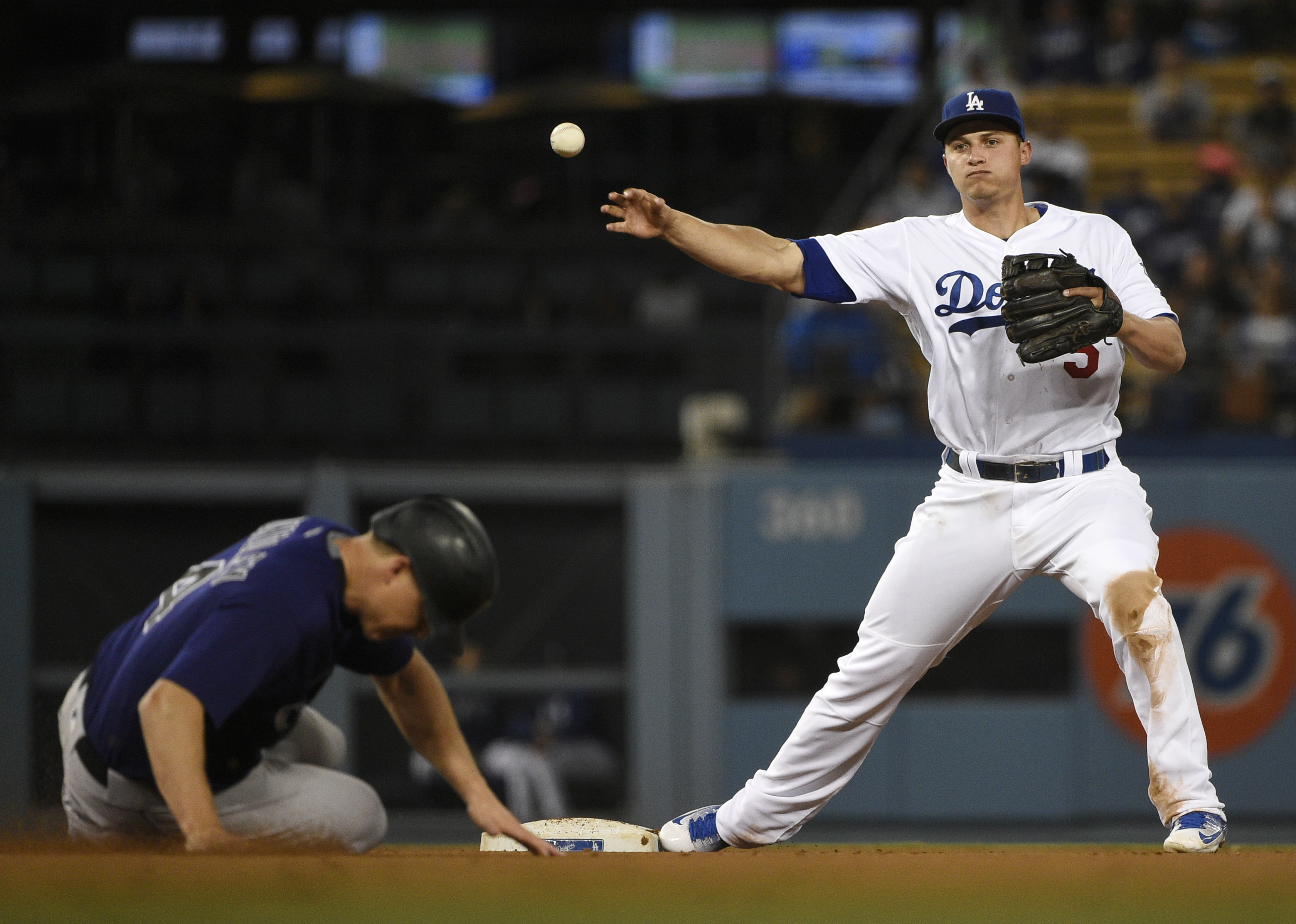 Los Angeles Dodgers shortstop Corey Seager, right, throws to first to complete a double play while Colorado Rockies' Nick Hundley, left, slide into second during the fifth inning of a baseball game in Los Angeles, Monday, June 6, 2016. (AP Photo/Kelvin Ku