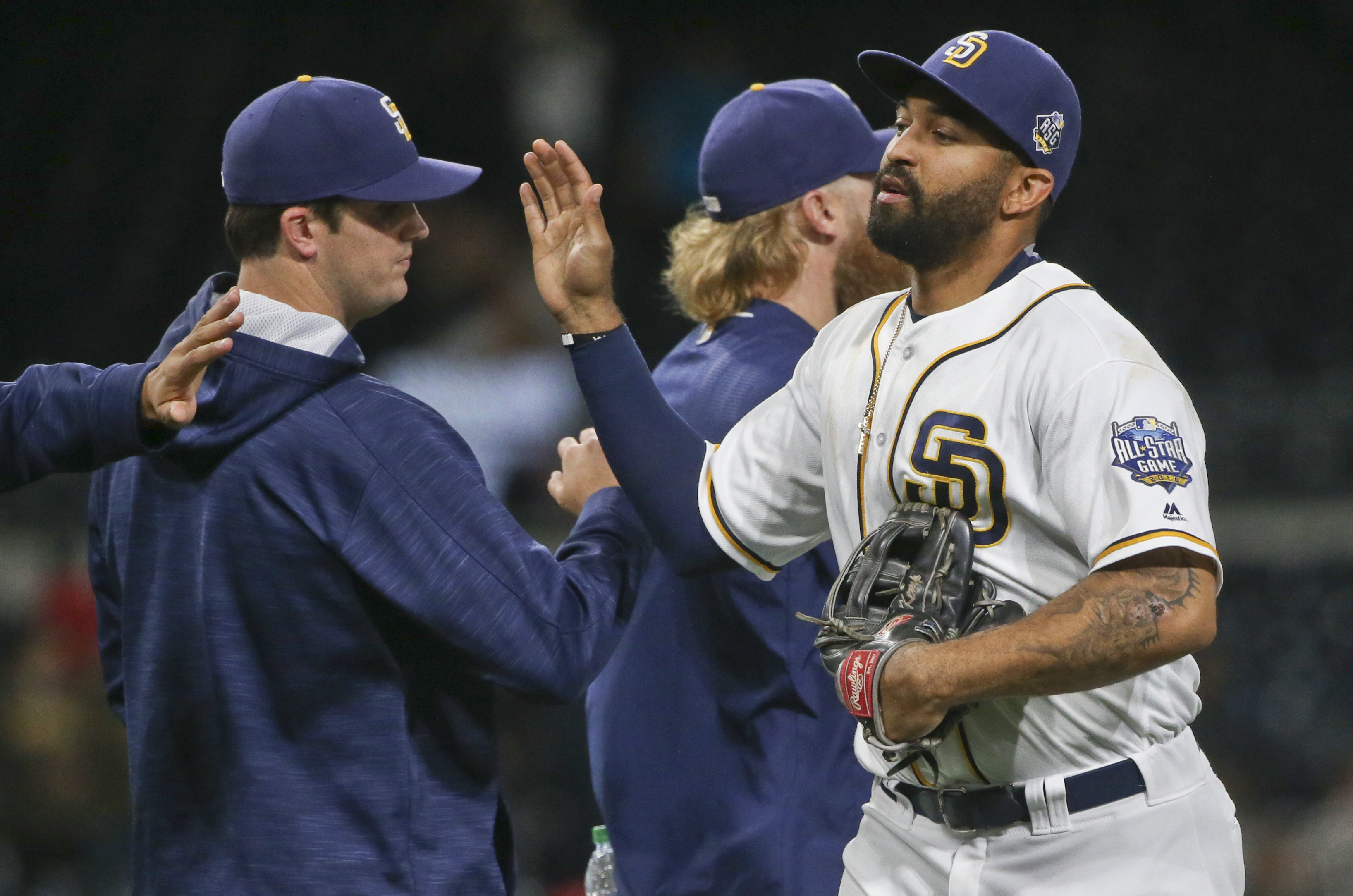 San Diego Padres' Matt Kemp, who had two hits and drove in two runs, high fives his way through teammates after the Padres 7-2 victory over the Atlanta Braves in a baseball game Monday, June 6, 2016, in San Diego. (AP Photo/Lenny Ignelzi)