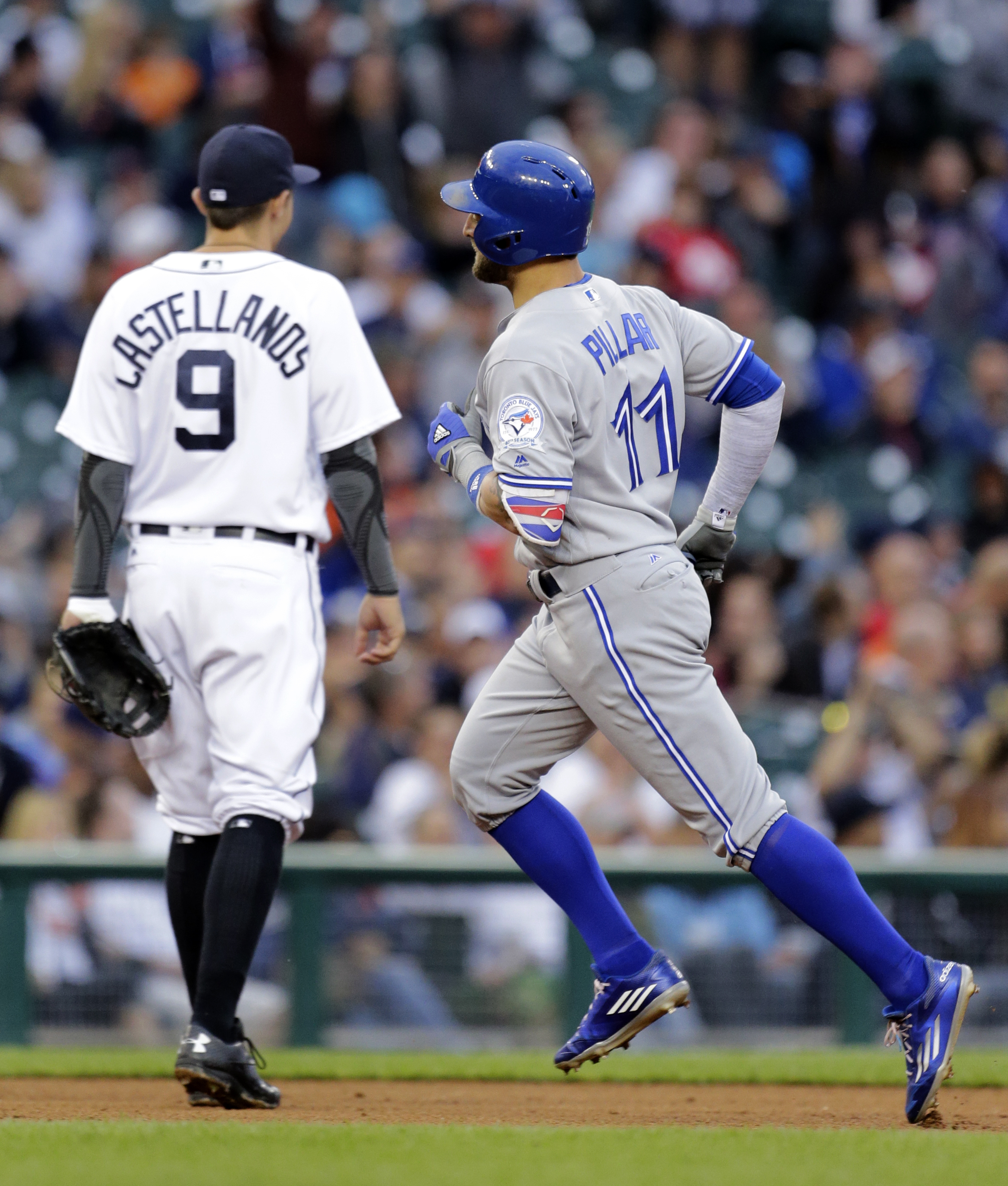 Toronto Blue Jays' Kevin Pillar (11) rounds the bases past Detroit Tigers third baseman Nick Castellanos after hitting a solo home run during the fifth inning of a baseball game Tuesday, June 7, 2016, in Detroit. (AP Photo/Duane Burleson)