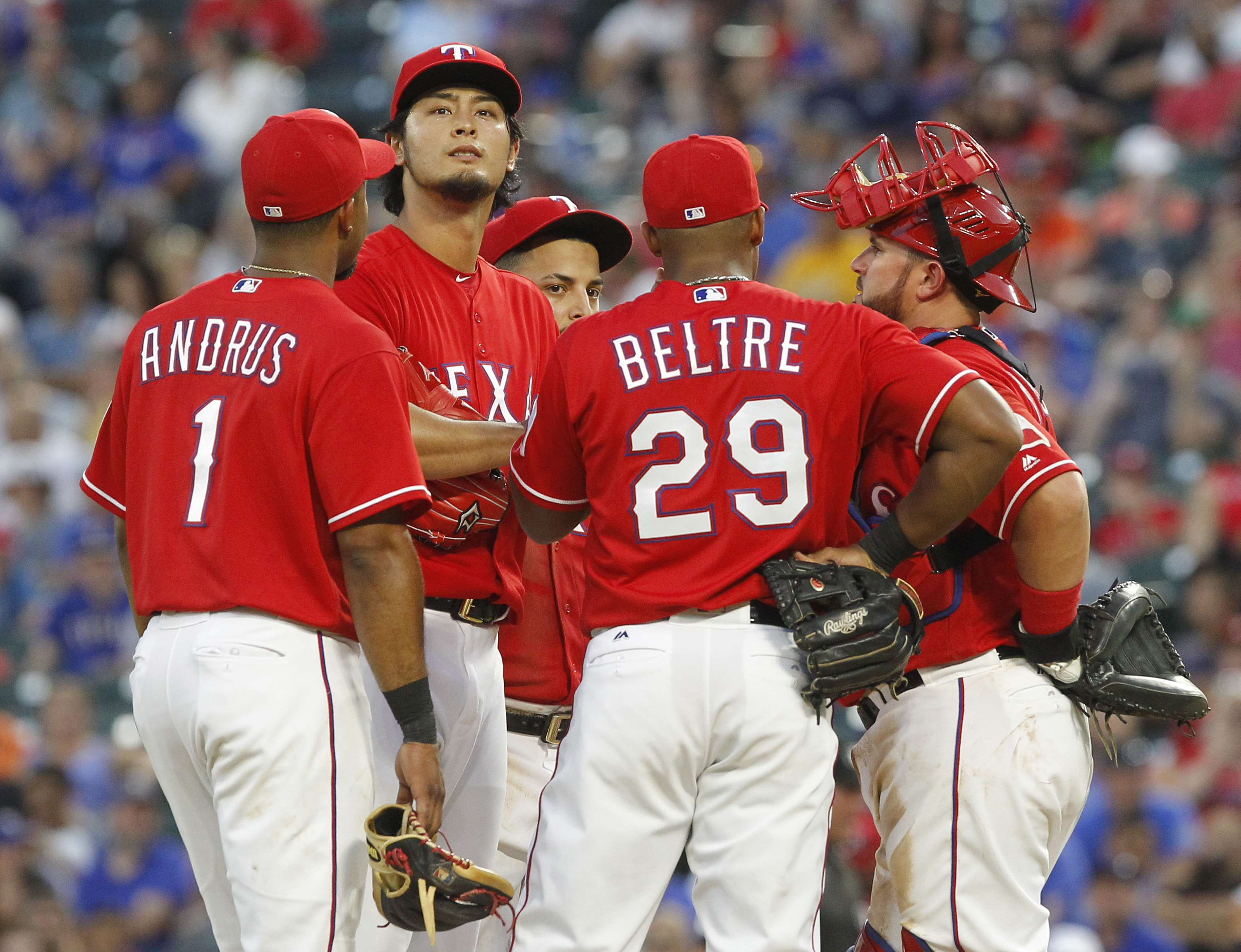 Texas Rangers pitcher Yu Darvish, second from left, meets with teammates on the mound during the fifth inning of a baseball game against the Houston Astros on Wednesday, June 8, 2016, in Arlington, Texas. Darvish did not return to the game for the sixth i