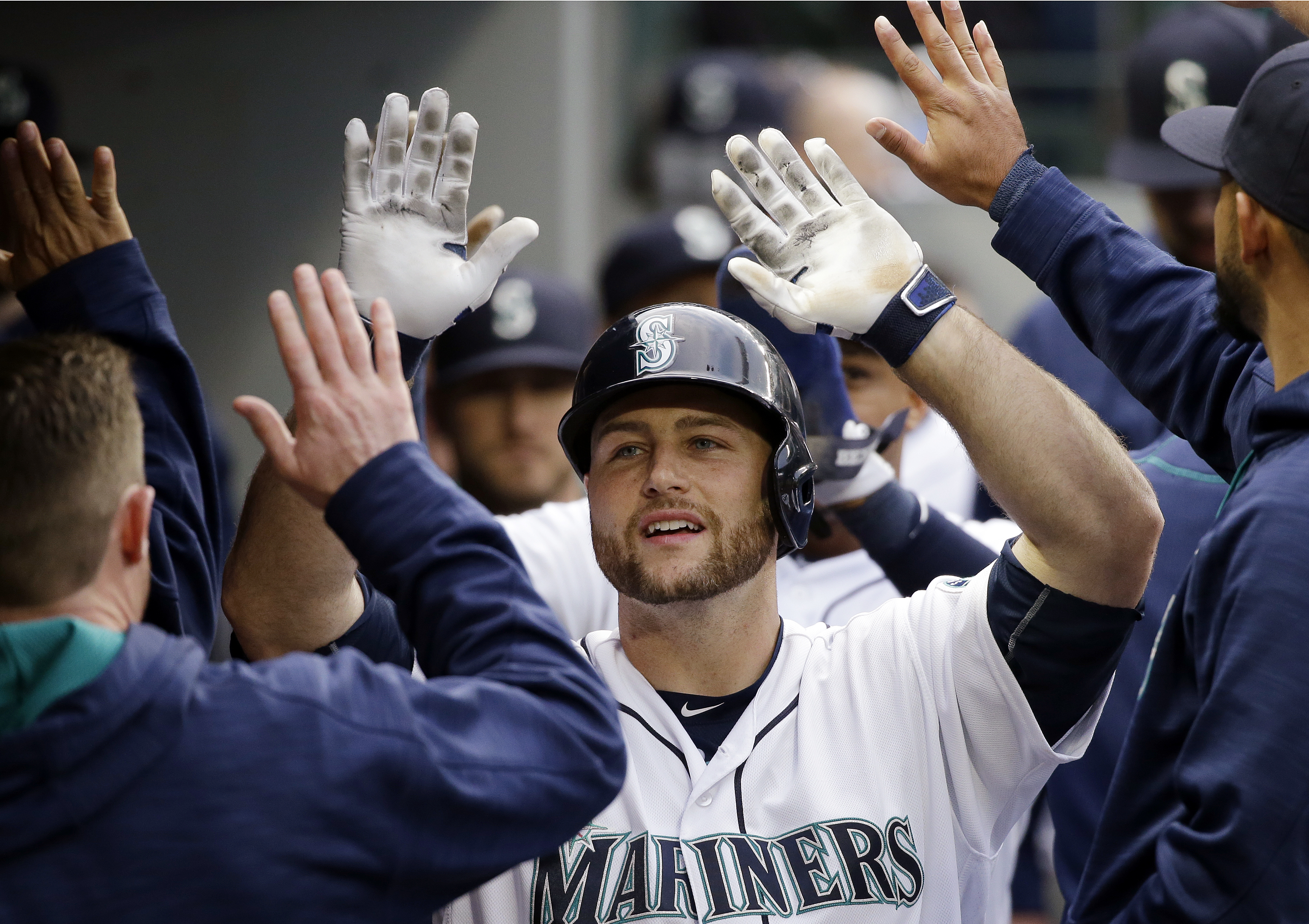 Seattle Mariners' Chris Iannetta is congratulated in the dugout after his two-run home run against the Cleveland Indians during the third inning of a baseball game Wednesday, June 8, 2016, in Seattle. (AP Photo/Elaine Thompson)