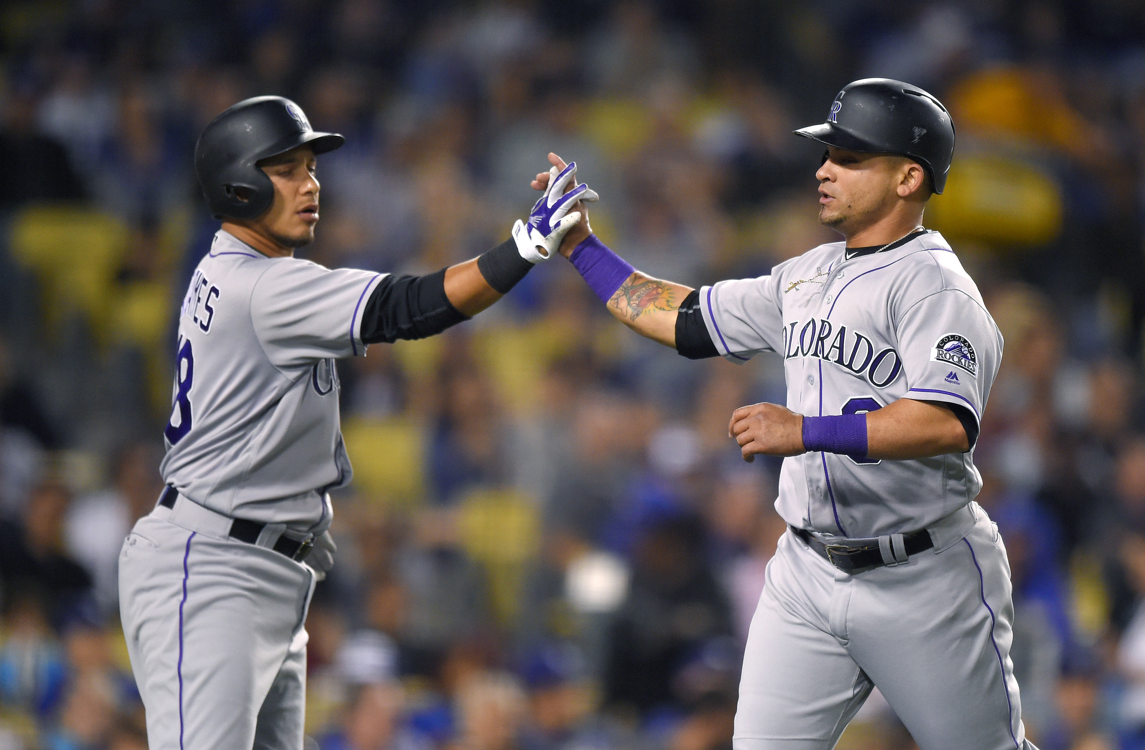 Colorado Rockies' Gerardo Parra, right, is congratulated by Cristhian Adames after scoring on a single by Daniel Descalso during the seventh inning of a baseball game against the Los Angeles Dodgers, Wednesday, June 8, 2016, in Los Angeles. (AP Photo/Mark