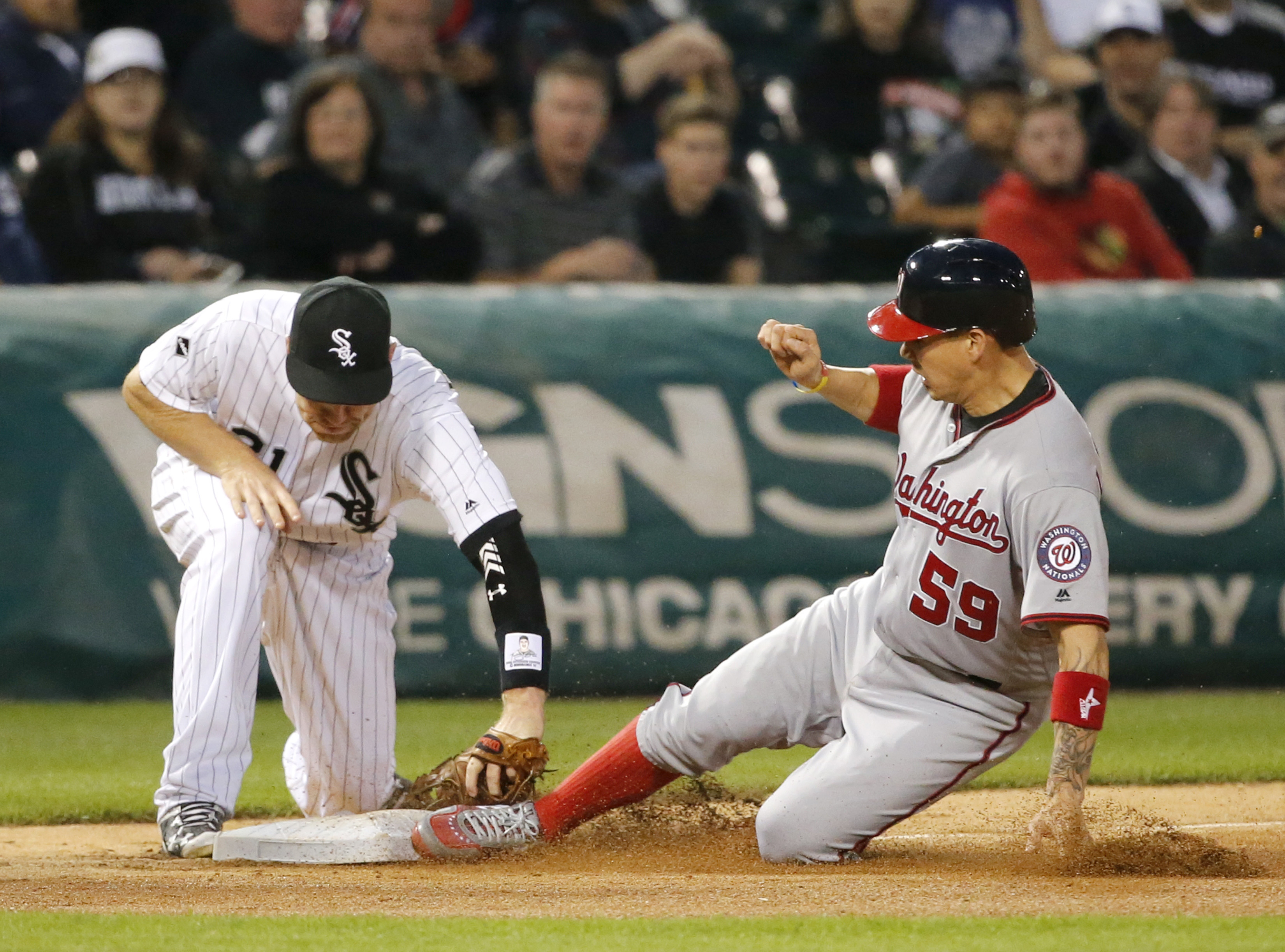 Washington Nationals' Jose Lobaton (59) slides safely into third as Chicago White Sox's Todd Frazier fields a throw from Melky Cabrera during the sixth inning of a baseball game Thursday, June 9, 2016, in Chicago. The Chicago White Sox challenged the safe