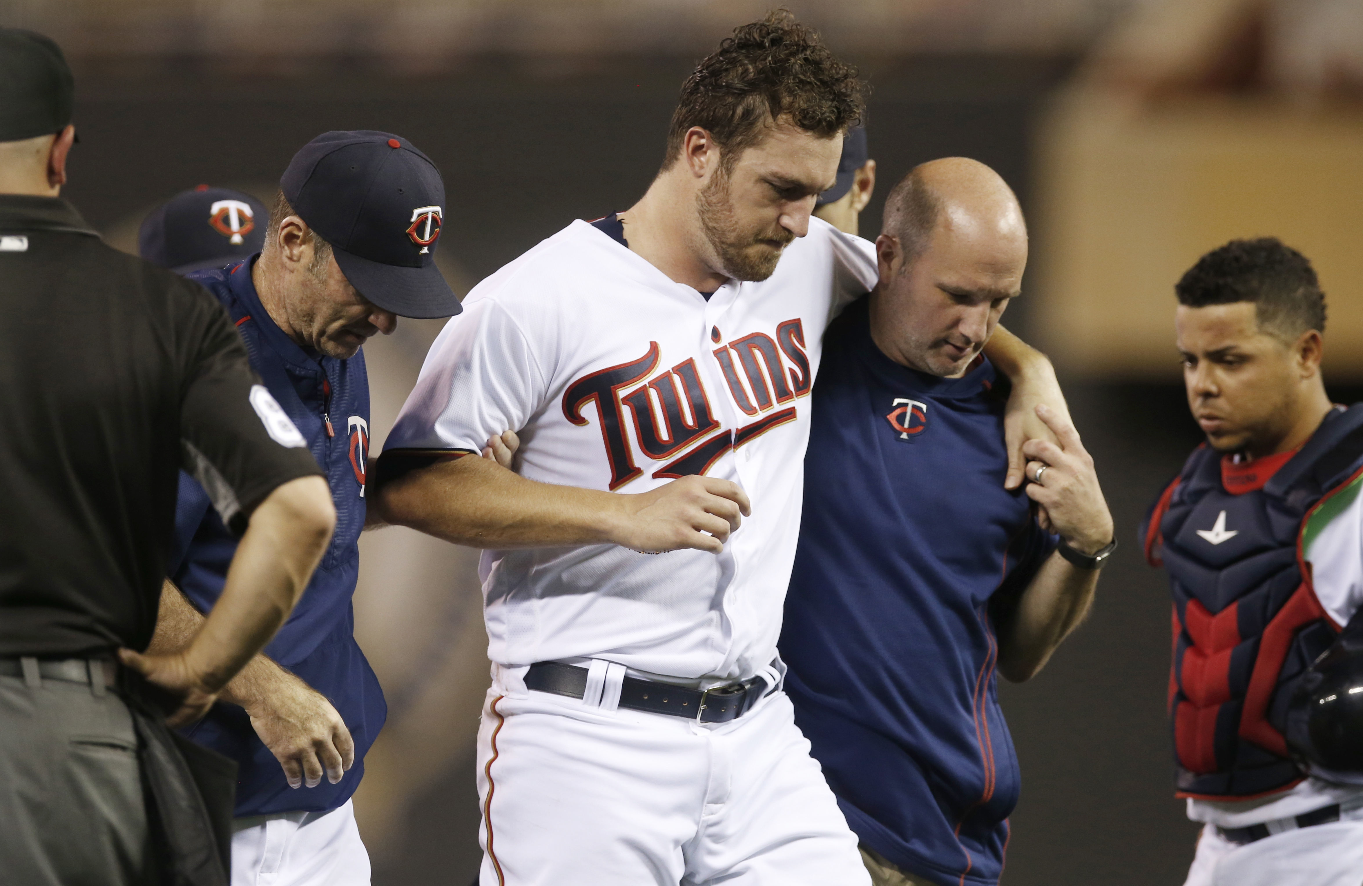 Minnesota Twins pitcher Phil Hughes is helped off the field by trainer Tony Leo, right, and manager Paul Molitor, left, after he was hit in the knee with a line drive by Miami Marlins' J.T. Realmuto during the ninth inning of a baseball game Thursday, Jun