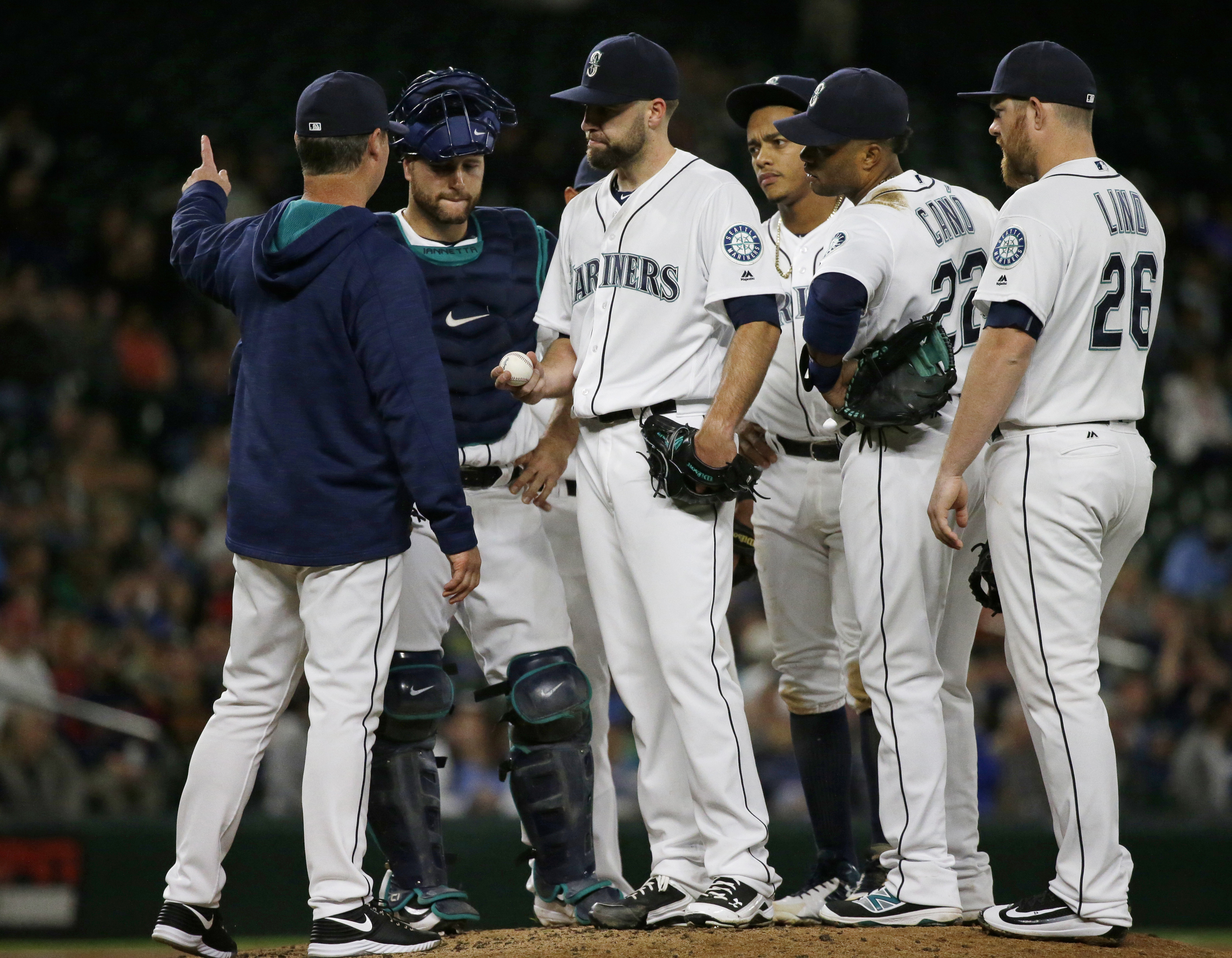 Seattle Mariners manager Scott Servais, left, signals for left-handed pitcher Mike Montgomery to come into the game and relieve starting pitcher Nathan Karns, center, during the fifth inning of a baseball game against the Cleveland Indians, Thursday, June