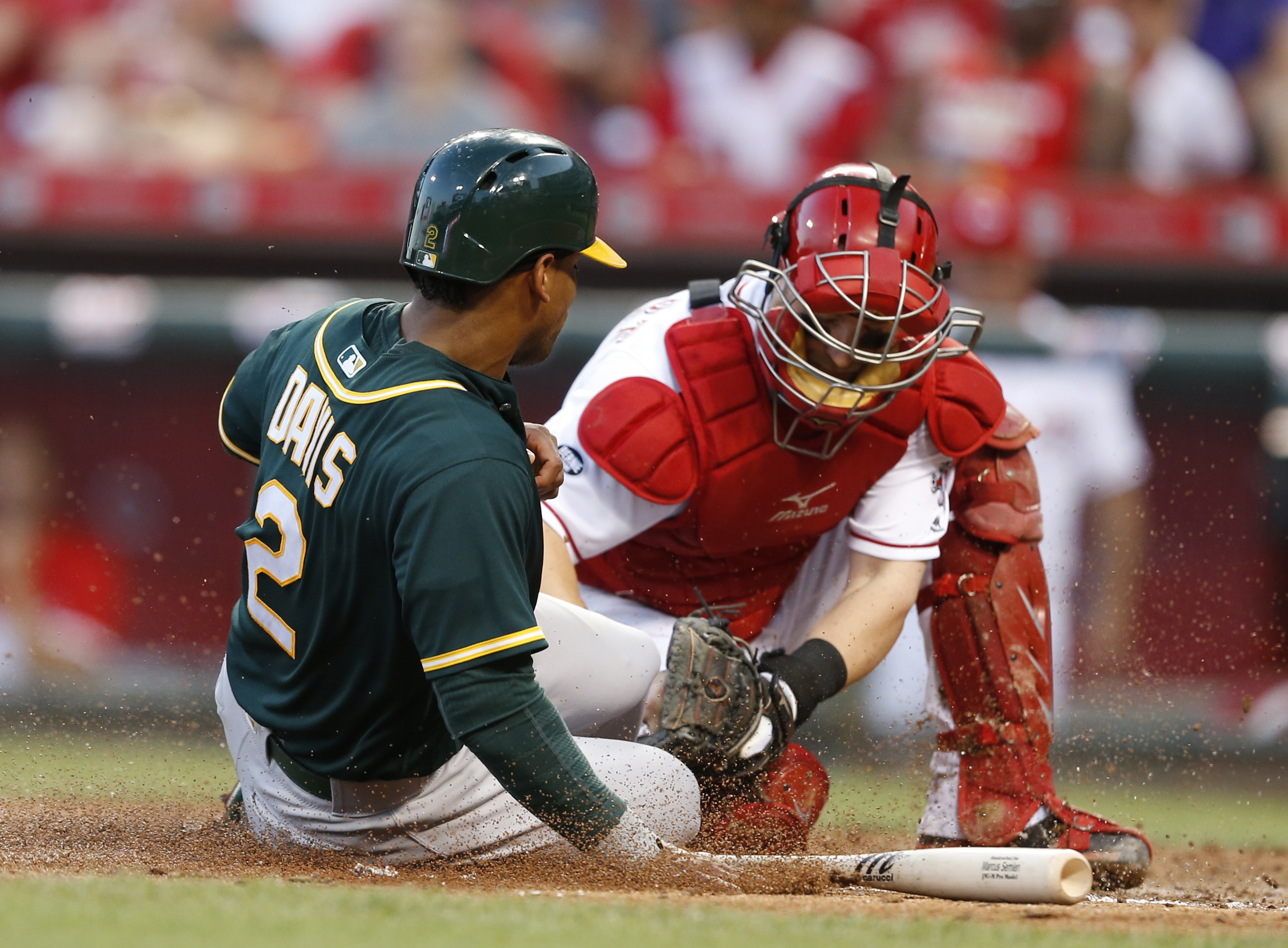 Oakland Athletics Khris Davis (2) is tagged out at the plate, attempting to score, by Cincinnati Reds catcher Tucker Barnhart during the sixth inning of a baseball game, Friday, June 10, 2016, in Cincinnati. (AP Photo/Gary Landers)