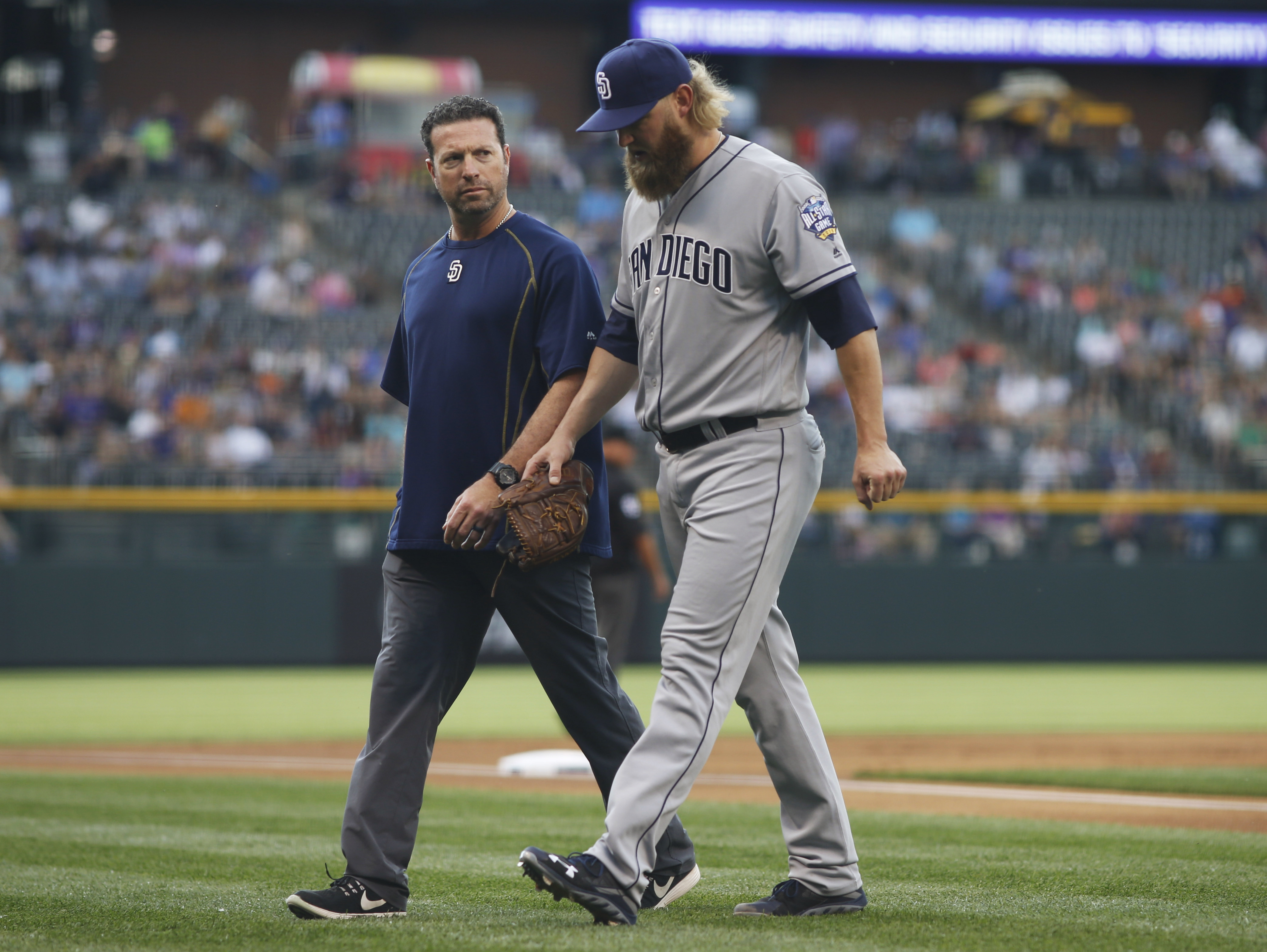 San Diego Padres head trainer Mark Rogow, left, accompanies San Diego Padres starting pitcher Andrew Cashner as they walk off the field after Cashner was pulled from the mound after striking out Colorado Rockies leadoff hitter Charlie Blackmon during the