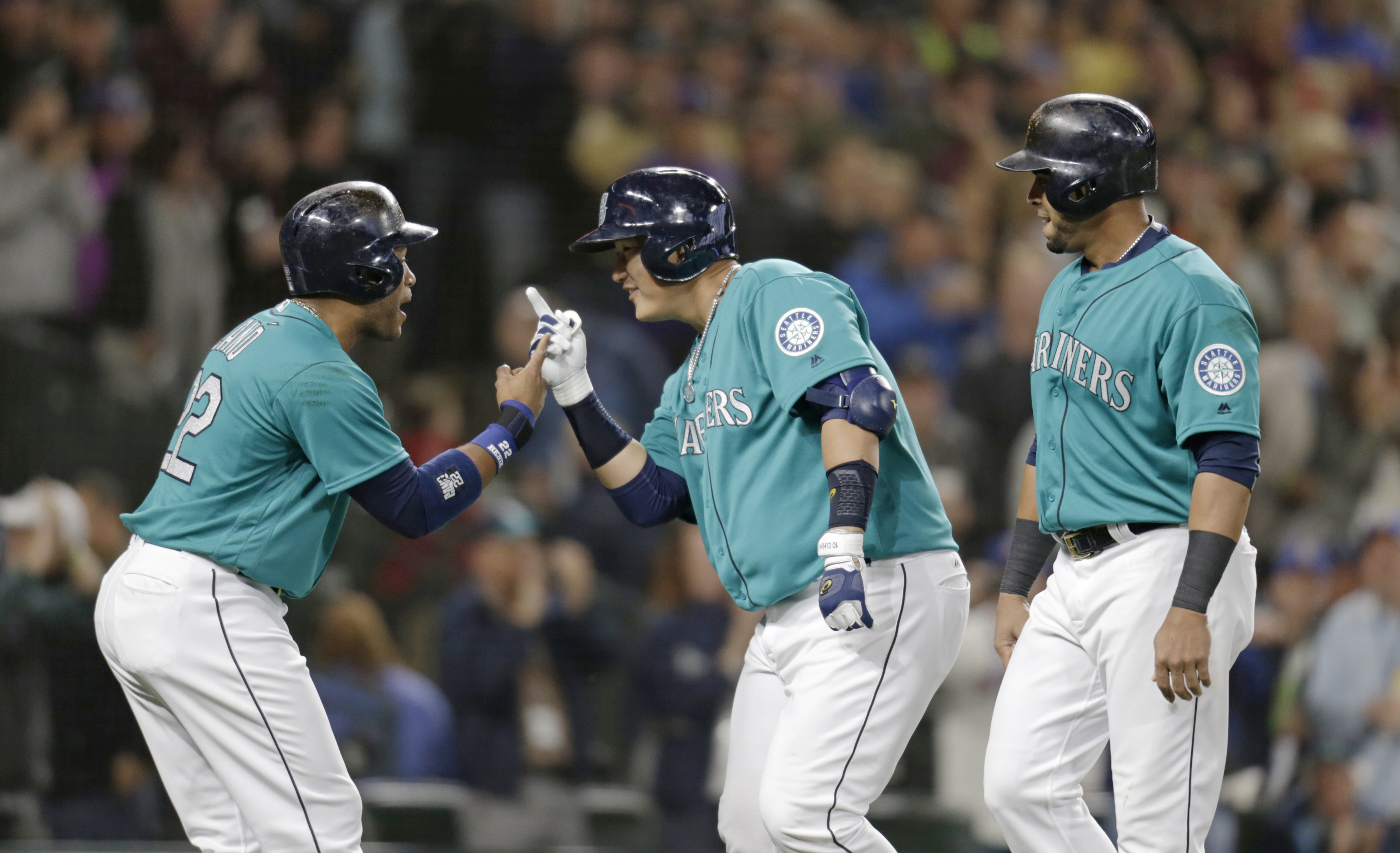 Seattle Mariners' Dae-Ho Lee, center, celebrates with Robinson Cano, left and Nelson Cruz, right, after hitting a three-run home run off Texas Rangers' Derek Holland during fourth inning of a baseball game Friday, June 10, 2016, in Seattle. (AP Photo/John