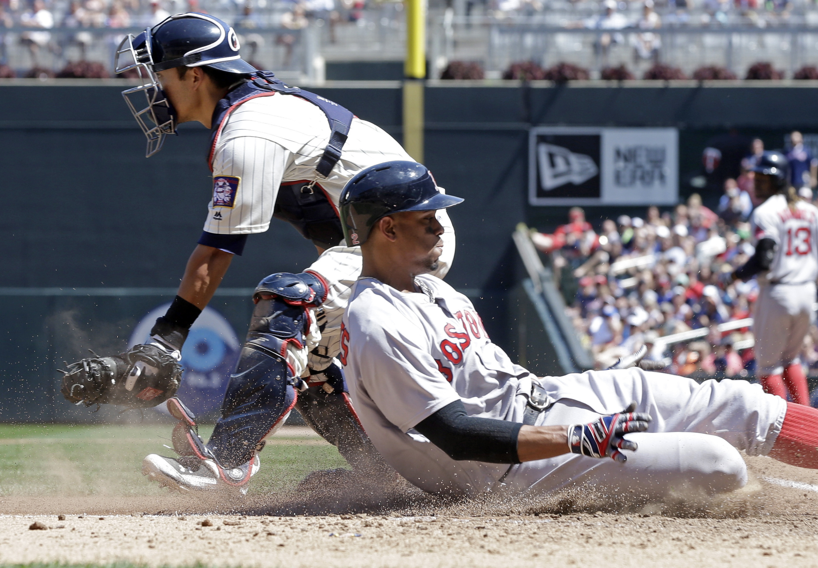 Boston Red Sox's Xander Bogaerts, right, scores from third on a go-ahead run past Minnesota Twins catcher Kurt Suzuki on a sacrifice fly by Hanley Ramirez in the sixth inning of a baseball game Saturday, June 11, 2016, in Minneapolis. (AP Photo/Jim Mone)