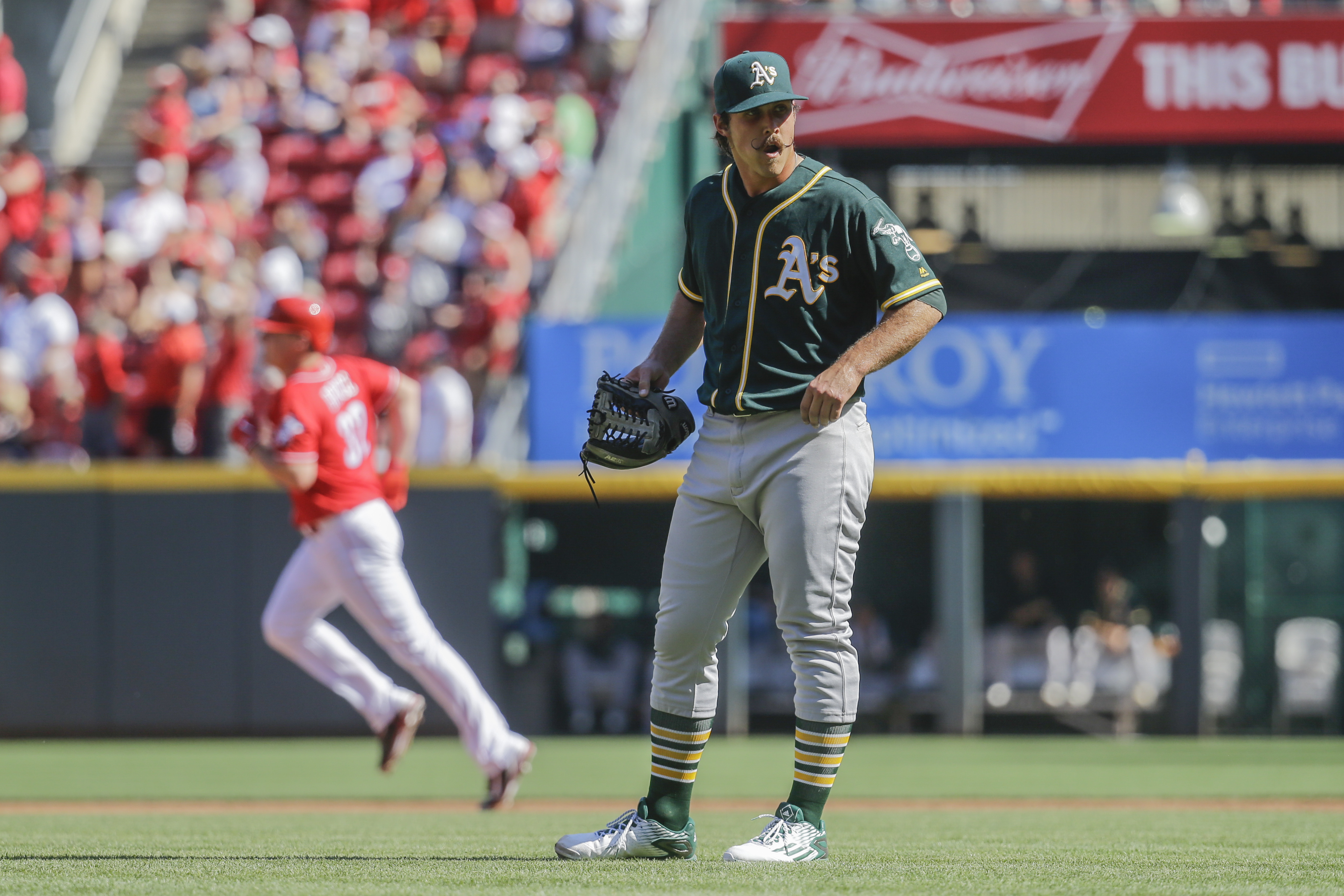 Oakland Athletics starting pitcher Daniel Mengden reacts after giving up a go-ahead two-run home run to Cincinnati Reds' Jay Bruce, left, in the third inning of baseball game, Saturday, June 11, 2016, in Cincinnati. (AP Photo/John Minchillo)