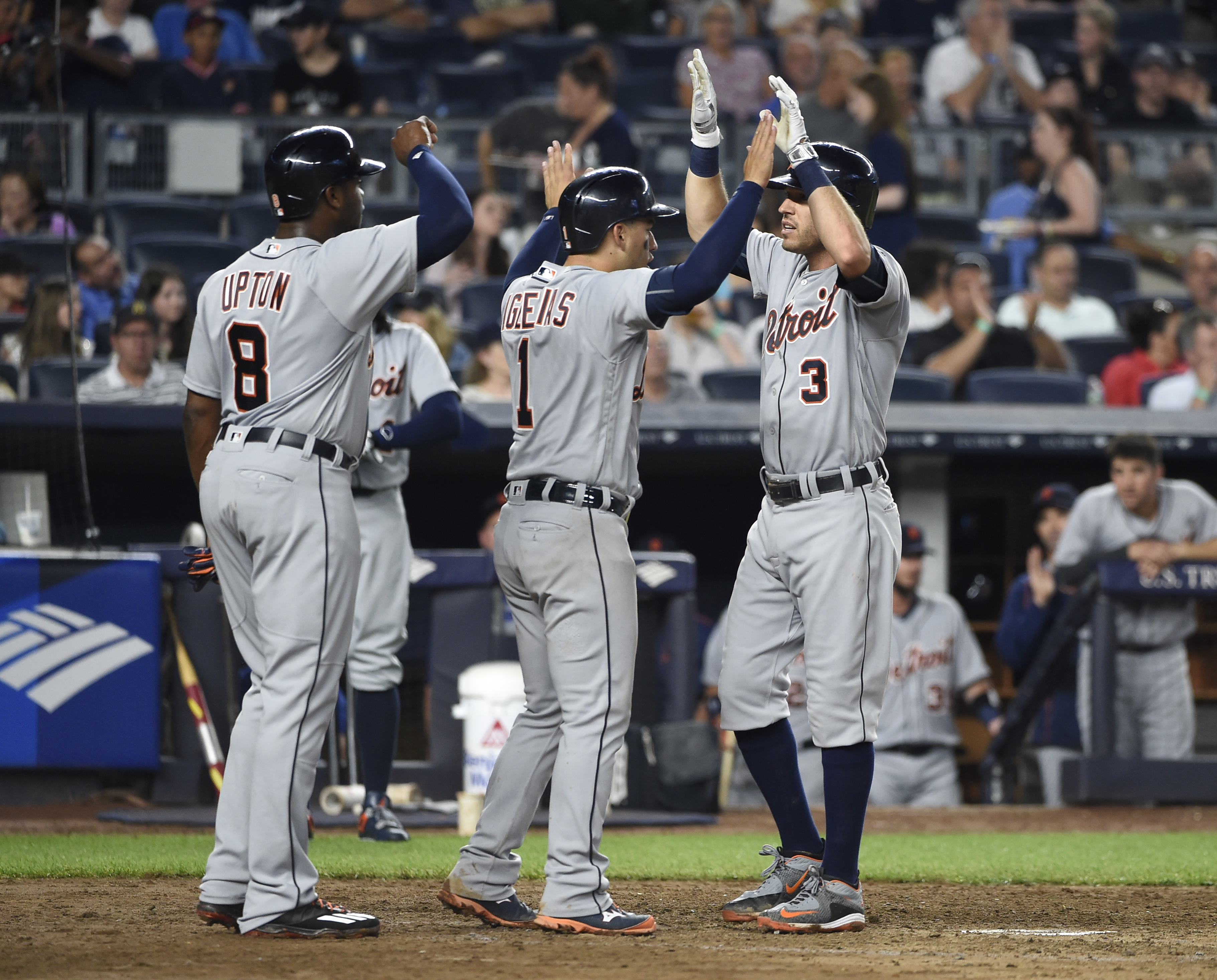 Detroit Tigers Ian Kinsler (3) is high-fived at home plate with Justin Upton (8) and Jose Iglesias (1) after Upton and Iglesias both scored on his three-run home run off New York Yankees starting pitcher Masahiro Tanaka in the fifth inning of a baseball g