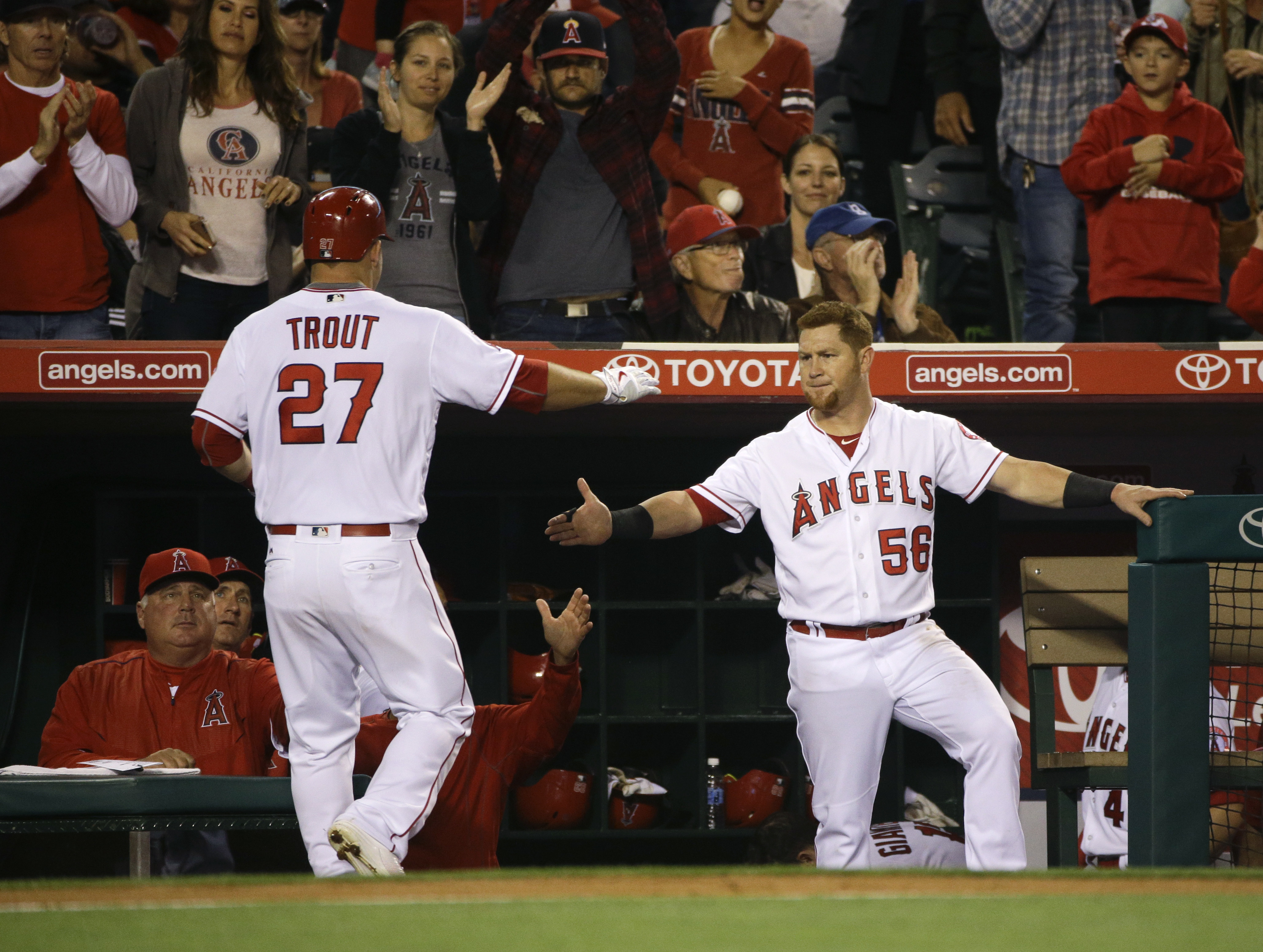 Los Angeles Angels' Mike Trout, left, is greeted by Kole Calhoun after scoring on a double by Jefry Marte during the fourth inning of a baseball game against the Cleveland Indians, Saturday, June 11, 2016, in Anaheim, Calif. (AP Photo/Jae C. Hong)
