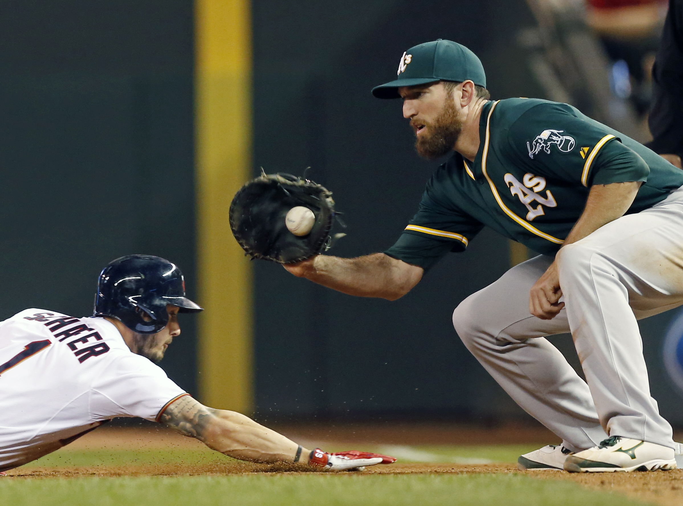 In this Monday, May 4, 2015 photo, Minnesota Twinsi Jordan Schafer, left, slides safely back to first to beat a pickoff attempt by Oakland Athletics first baseman Ike Davis in the fourth inning of a baseball game in Minneapolis. The New York Yankees are t