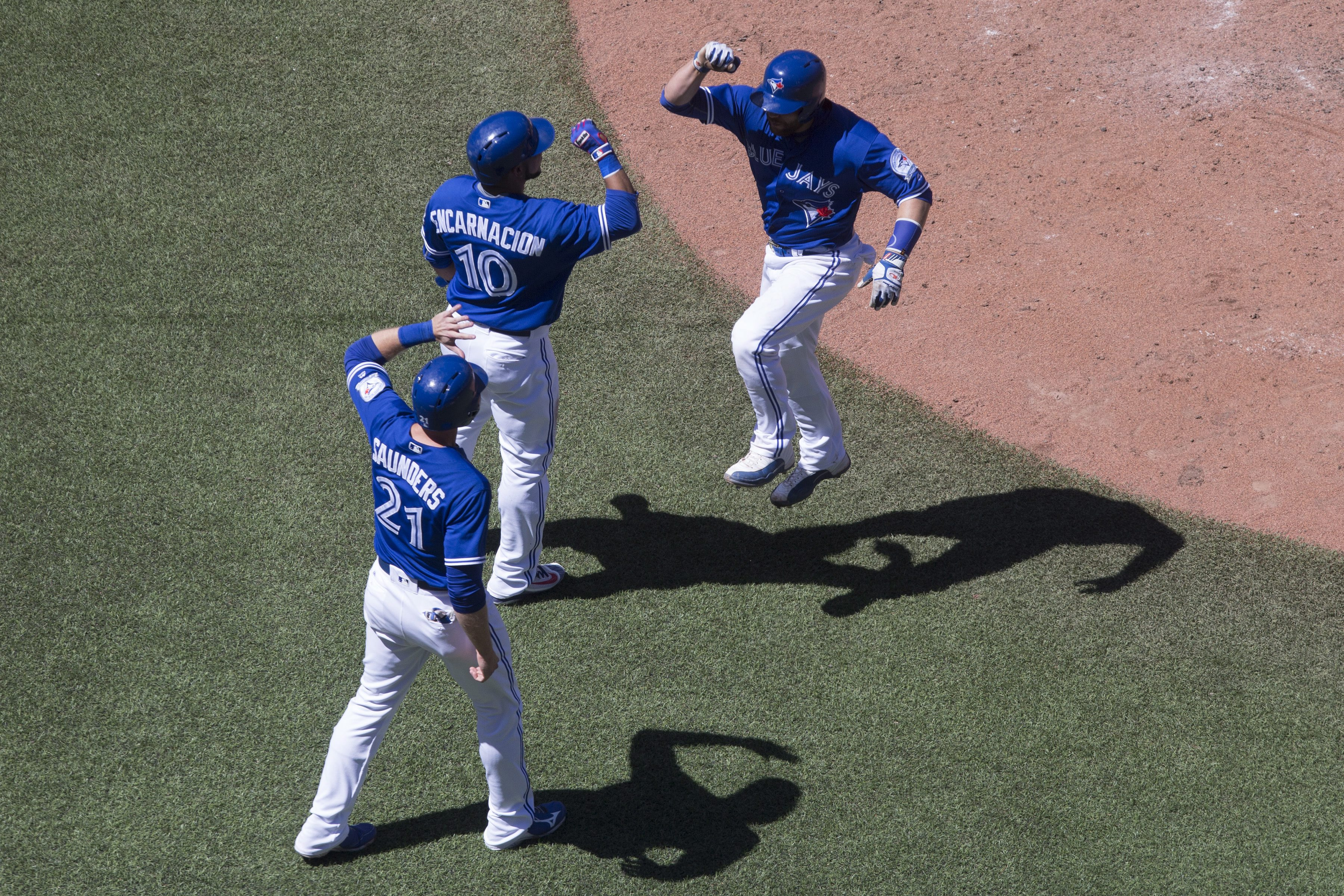 Toronto Blue Jays' Russell Martin, right, celebrates with Edwin Encarnation, center,and Michael Saunders after hitting a three-run home run off Baltimore Orioles relief pitcher Mychal Givens during sixth-inning baseball game action in Toronto, Sunday, Jun