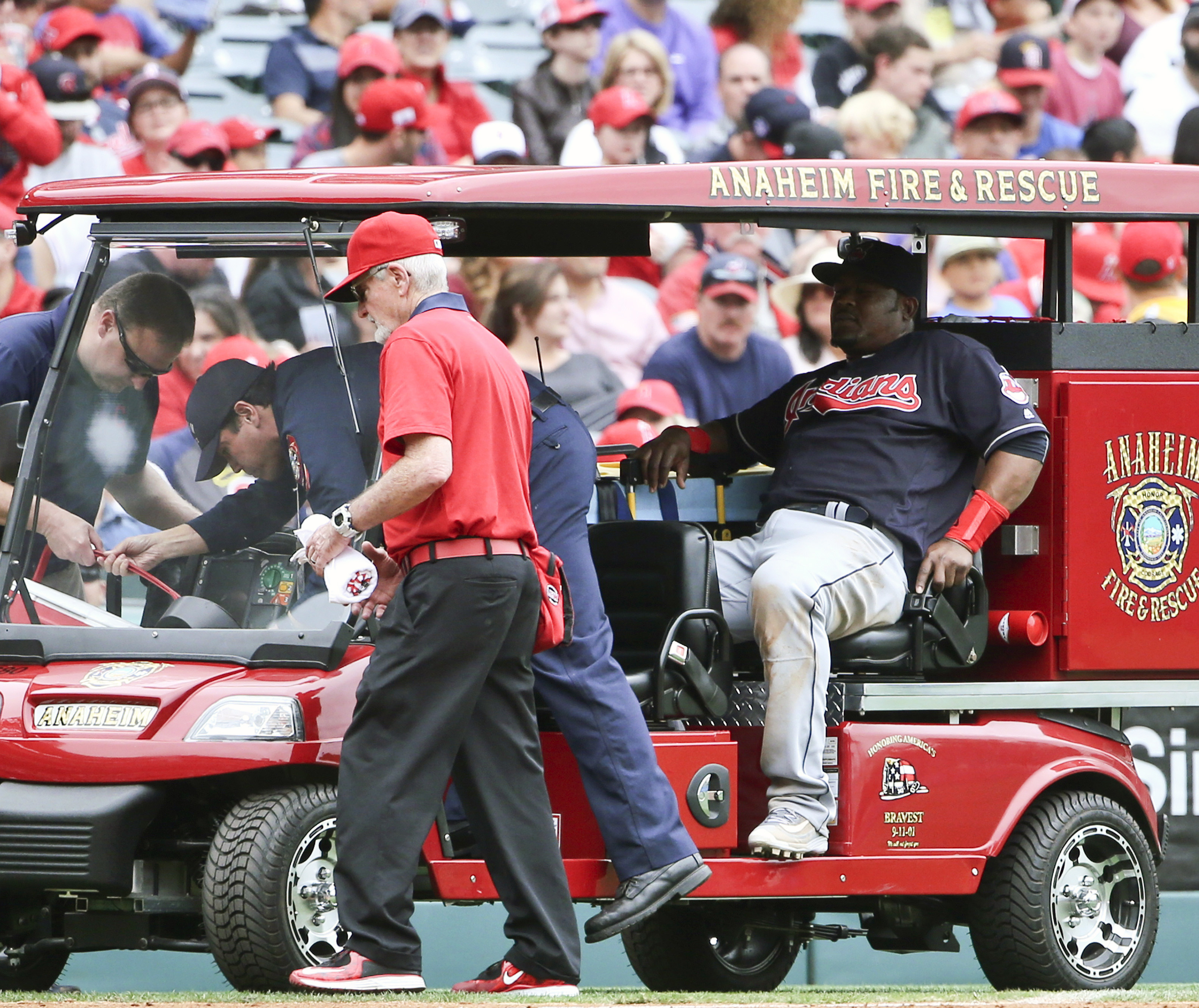Cleveland Indians third baseman Juan Uribe sits in the back of a cart after being injured while fielding a ground ball in the fourth inning of a baseball game against the Los Angeles Angels, Sunday, June 12, 2016, in Anaheim, Calif. Uribe left the game. (