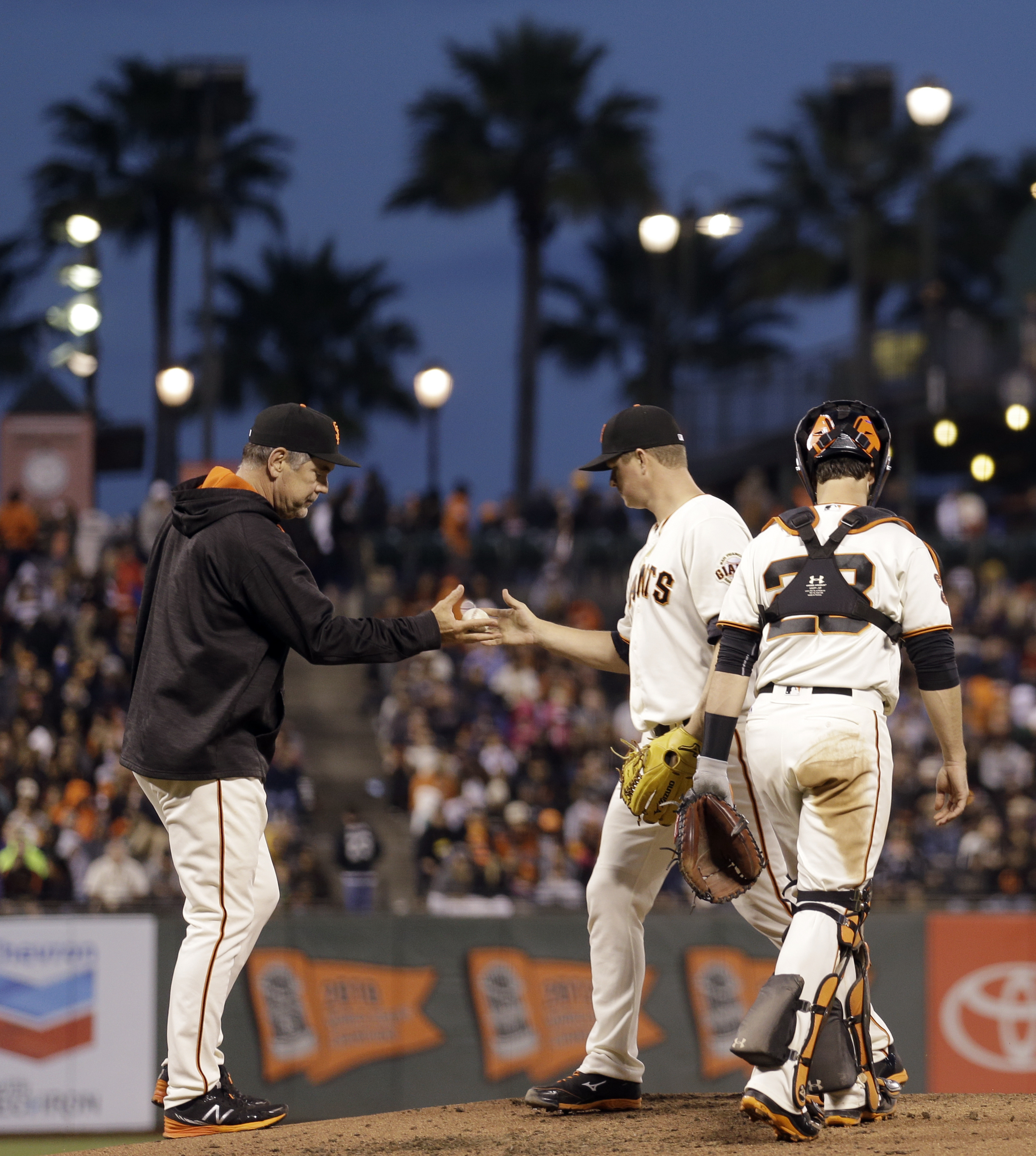 San Francisco Giants pitcher Matt Cain, center, hands the ball to manager Bruce Bochy during the fourth inning of a baseball game against the Milwaukee Brewers on Monday, June 13, 2016, in San Francisco. (AP Photo/Ben Margot)