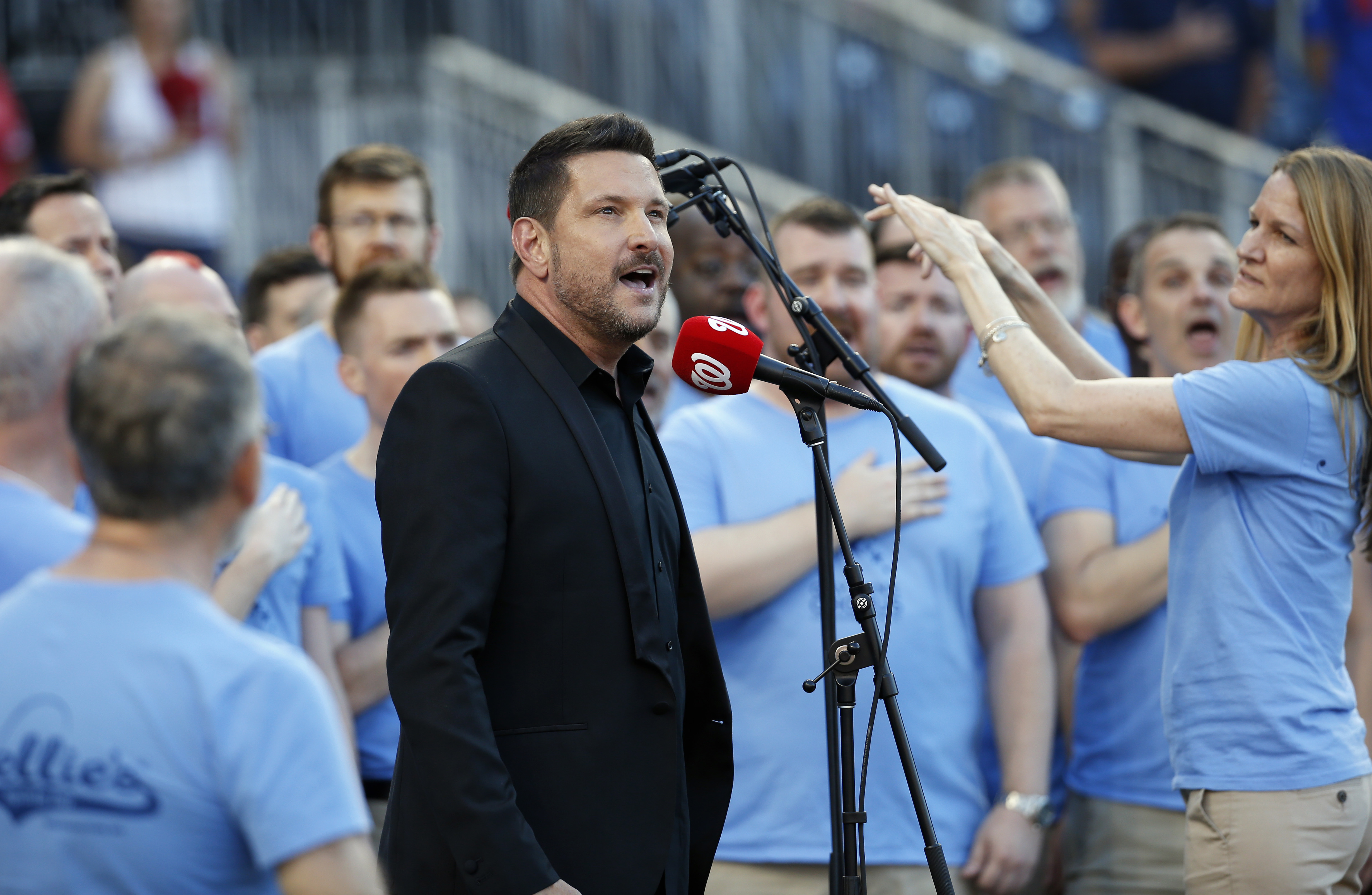 Ty Herndon, center, with the Gay Men's Chorus of Washington, sings the national anthem before a baseball game between the Washington Nationals and the Chicago Cubs at Nationals Park, Tuesday, June 14, 2016, in Washington. The Washington Nationals are host