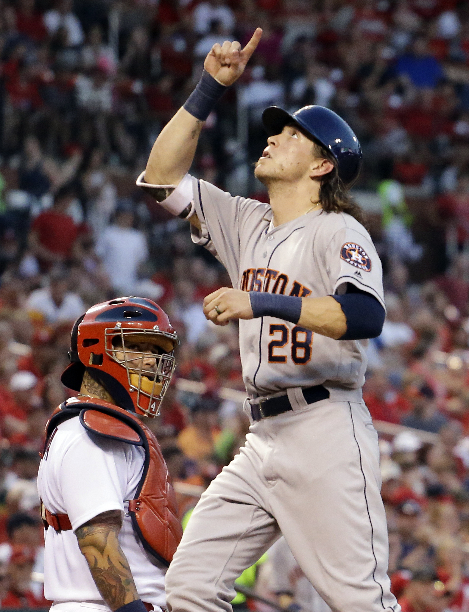 Houston Astros' Colby Rasmus celebrates after hitting a solo home run, next to St. Louis Cardinals catcher Yadier Molina during the fifth inning of a baseball game Tuesday, June 14, 2016, in St. Louis. (AP Photo/Jeff Roberson)