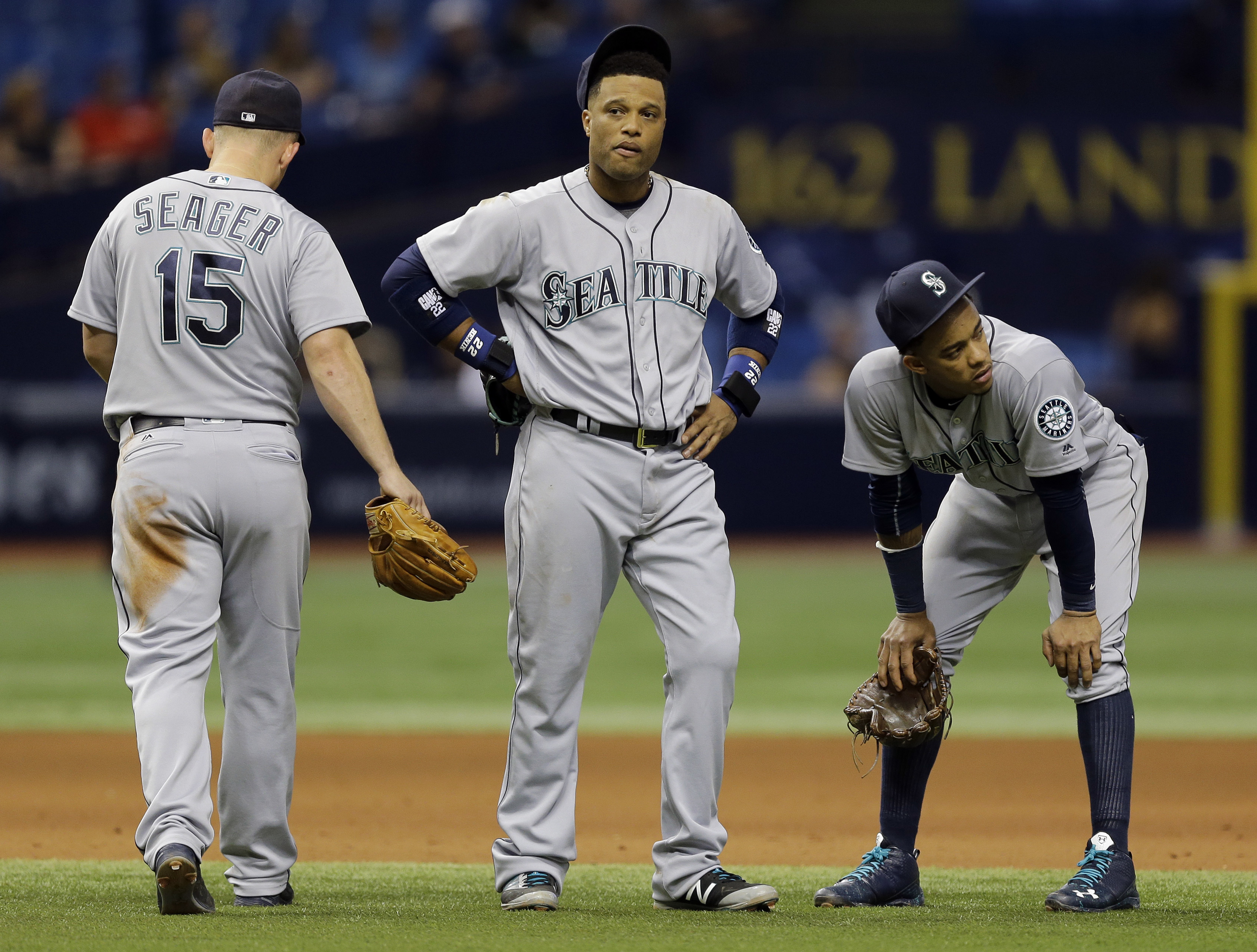Seattle Mariners third baseman Kyle Seager, left, second baseman Robinson Cano, center, and shortstop Ketel Marte react after Tampa Bay Rays' Evan Longoria hit a three-run home run off relief pitcher Nick Vincent during the seventh inning of a baseball ga