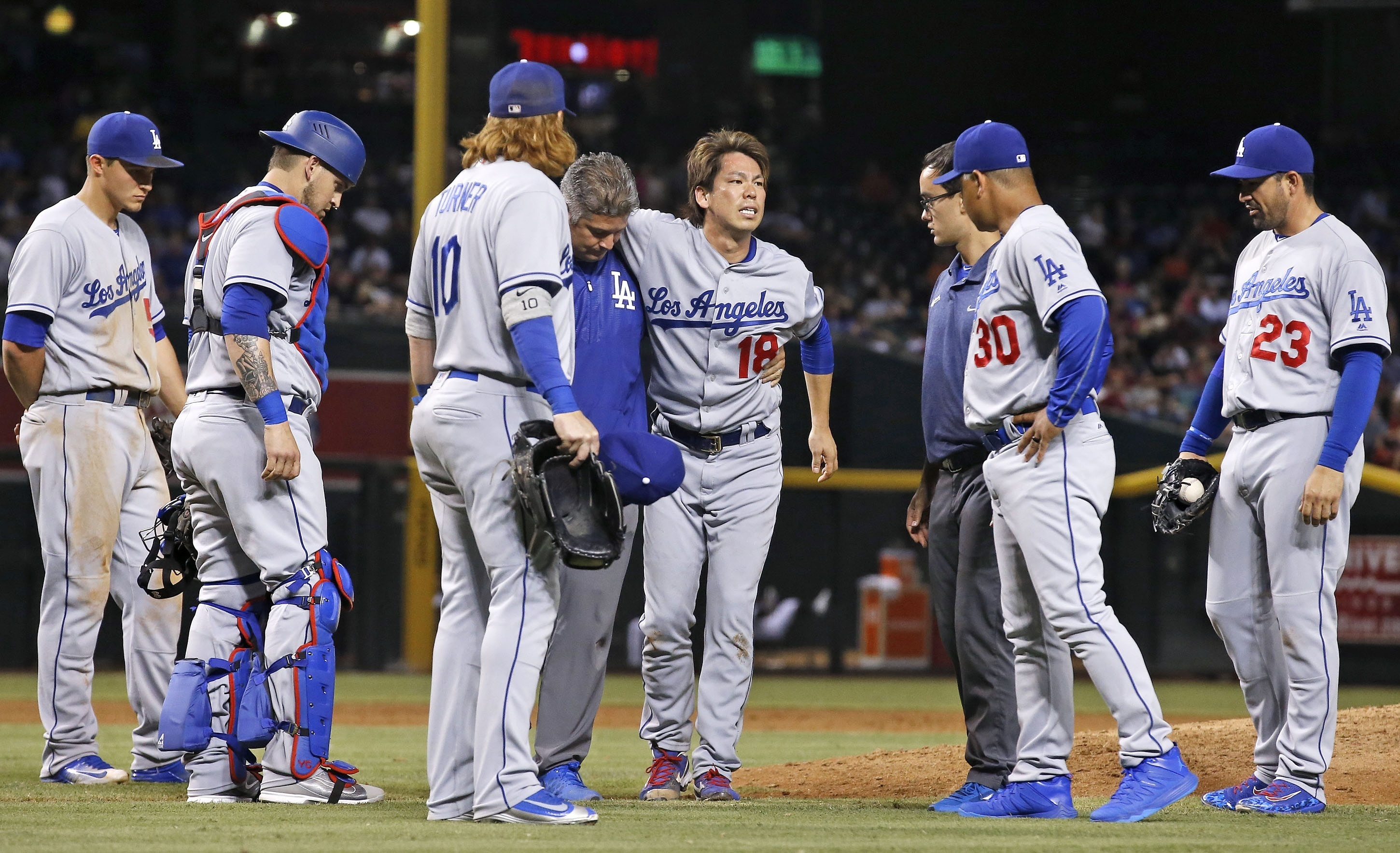 After being hit in the right leg by a batted ball from Arizona Diamondbacks' Paul Goldschmidt, Los Angeles Dodgers' Kenta Maeda (18) grimaces as he is helped off of the field by training staff as manager Dave Roberts (30), Adrian Gonzalez (23), Justin Tur