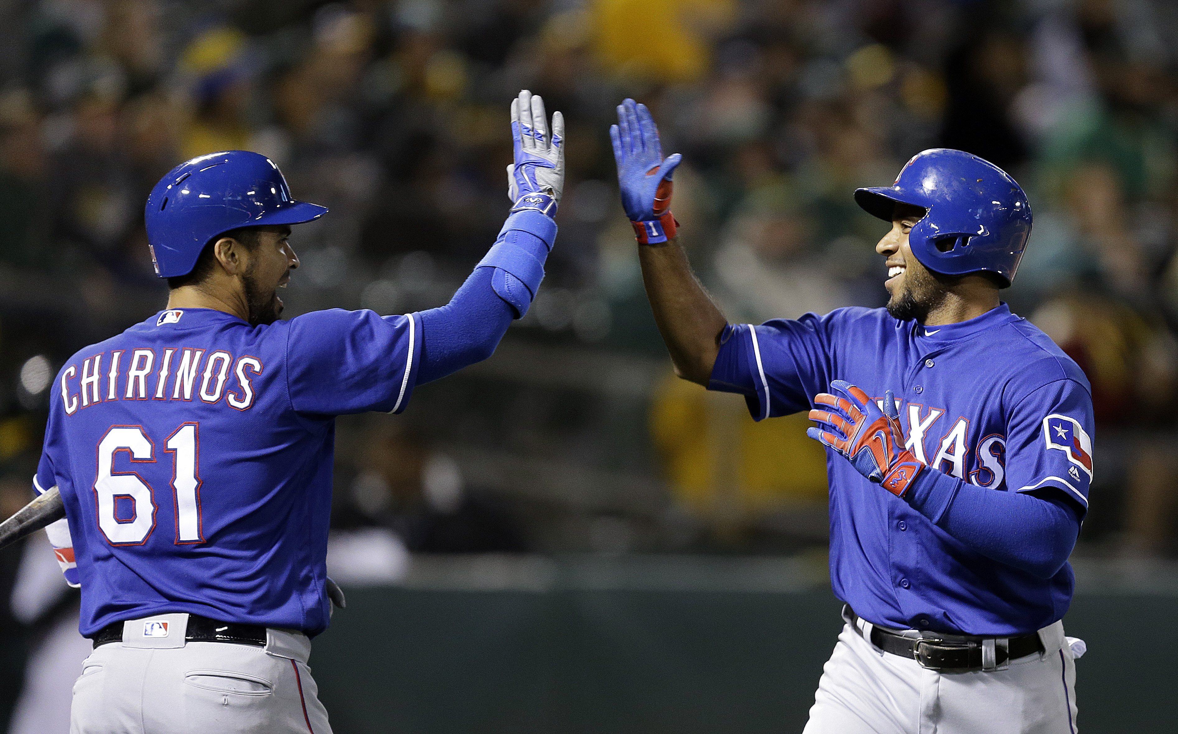 Texas Rangers' Elvis Andrus, right, celebrates with Robinson Chirinos (61) after hitting a home run against the Oakland Athletics during the eighth inning of a baseball game Tuesday, June 14, 2016, in Oakland, Calif. (AP Photo/Ben Margot)