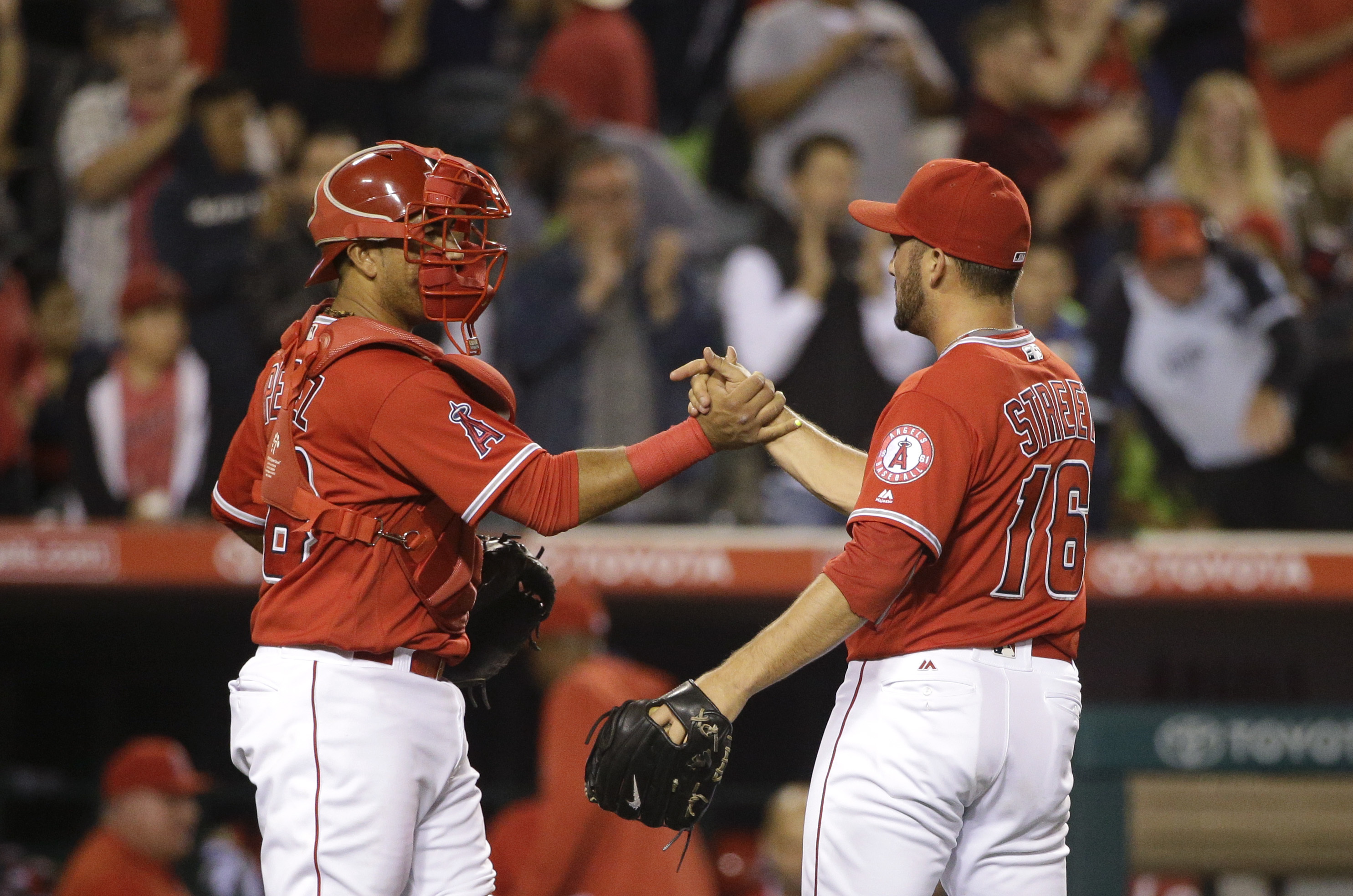 Los Angeles Angels relief pitcher Huston Street, right, and catcher Carlos Perez celebrate the team's 5-4 win against the Minnesota Twins in a baseball game,Tuesday, June 14, 2016, in Anaheim, Calif. (AP Photo/Jae C. Hong)