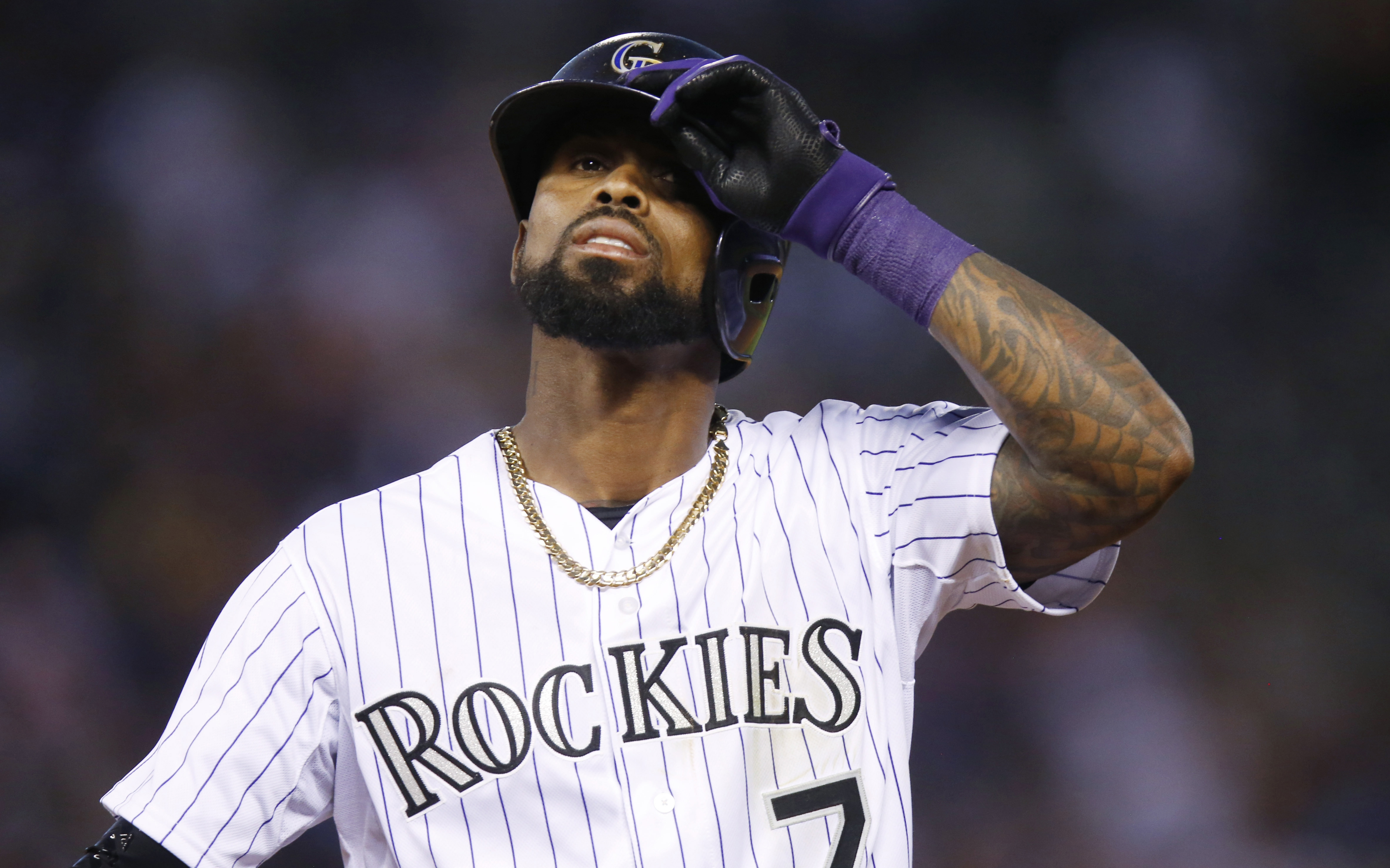 FILE - In this Aug. 4, 2015, file photo, Colorado Rockies shortstop Jose Reyes is shown adjusting his helmet while facing the Seattle Mariners in an interleague baseball game. Rather than activate  Reyes following his domestic violence suspension, the  Ro
