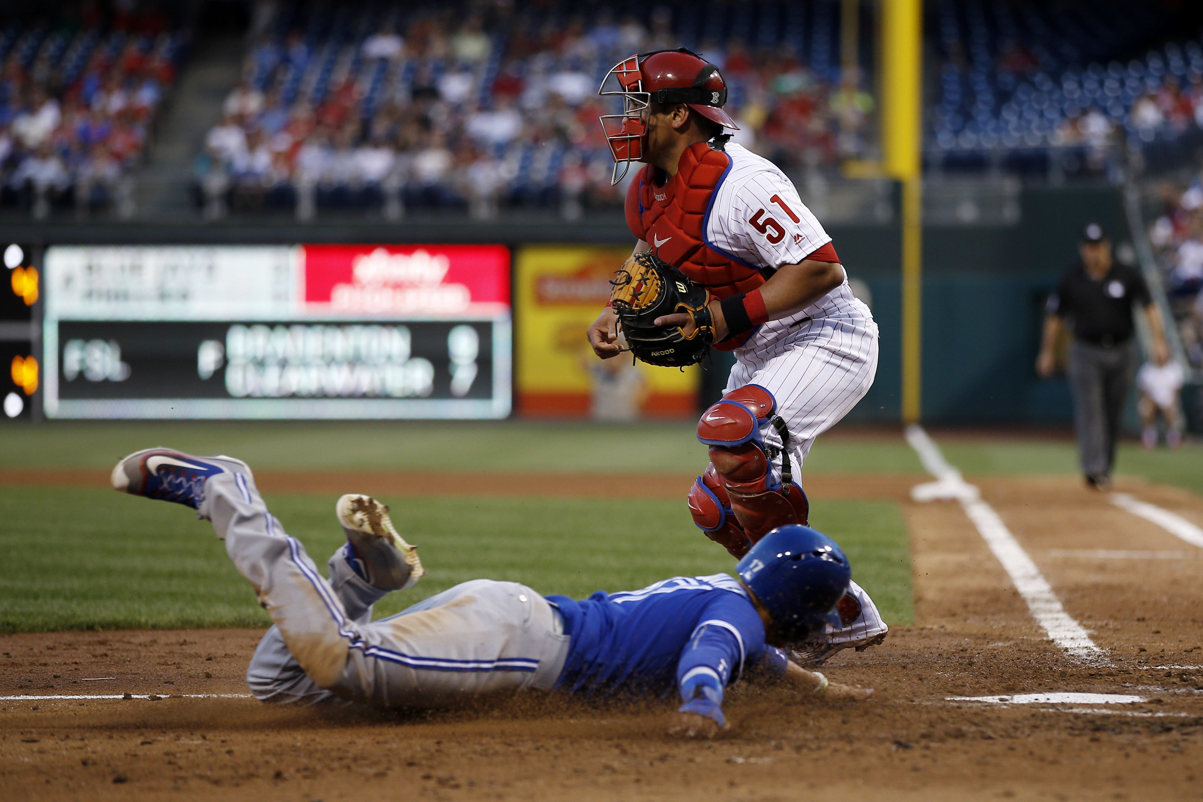 Toronto Blue Jays' Ryan Goins, bottom, scores past Philadelphia Phillies catcher Carlos Ruiz on a double by Devon Travis during the fourth inning of a baseball game, Wednesday, June 15, 2016, in Philadelphia. Travis was tagged out trying to advance to thi