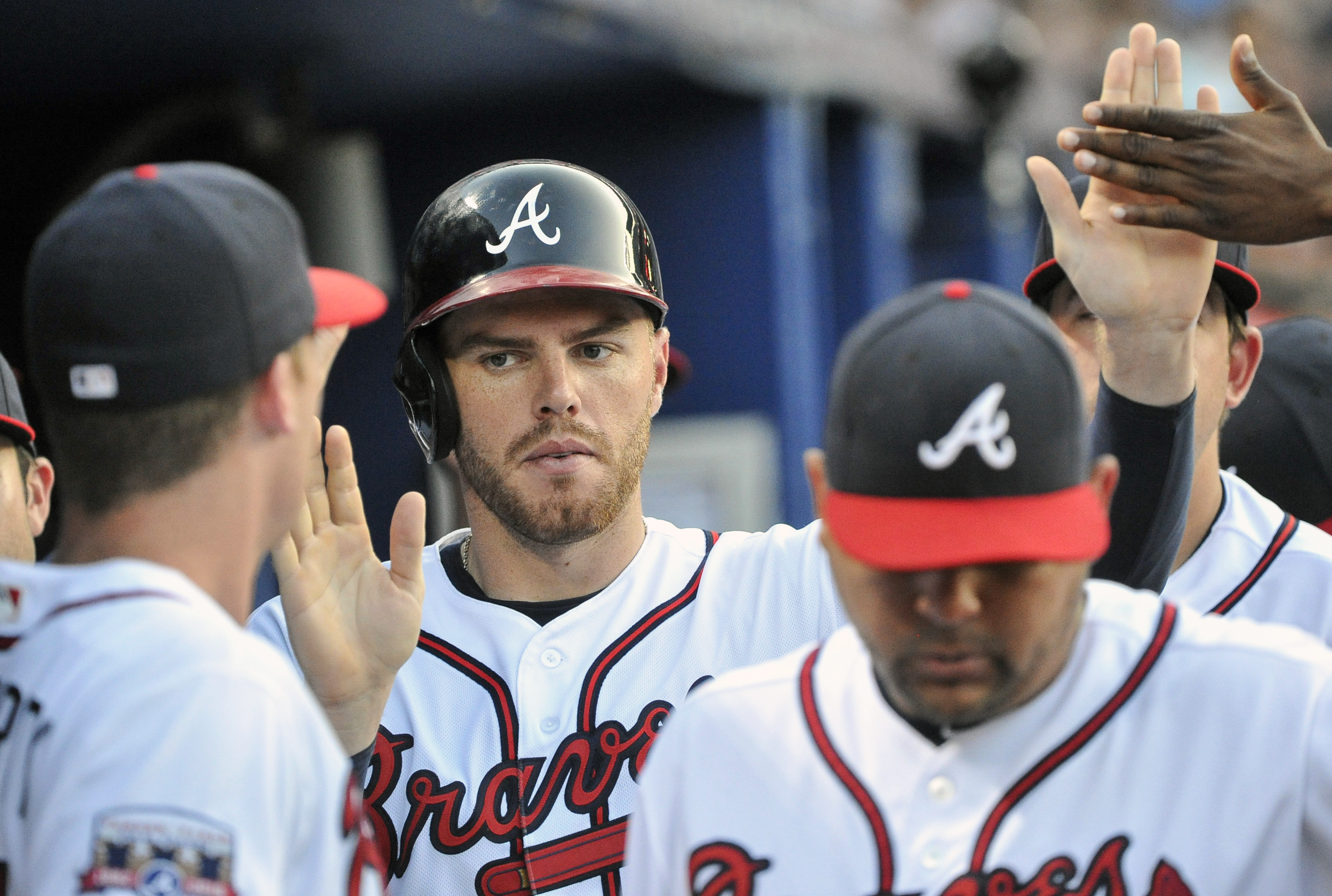 Atlanta Braves' Freddie Freeman is congratulated in the dugout after scoring against the Cincinnati Reds during the fourth inning of a baseball game, Wednesday, June 15, 2016, in Atlanta. (AP Photo/John Amis)