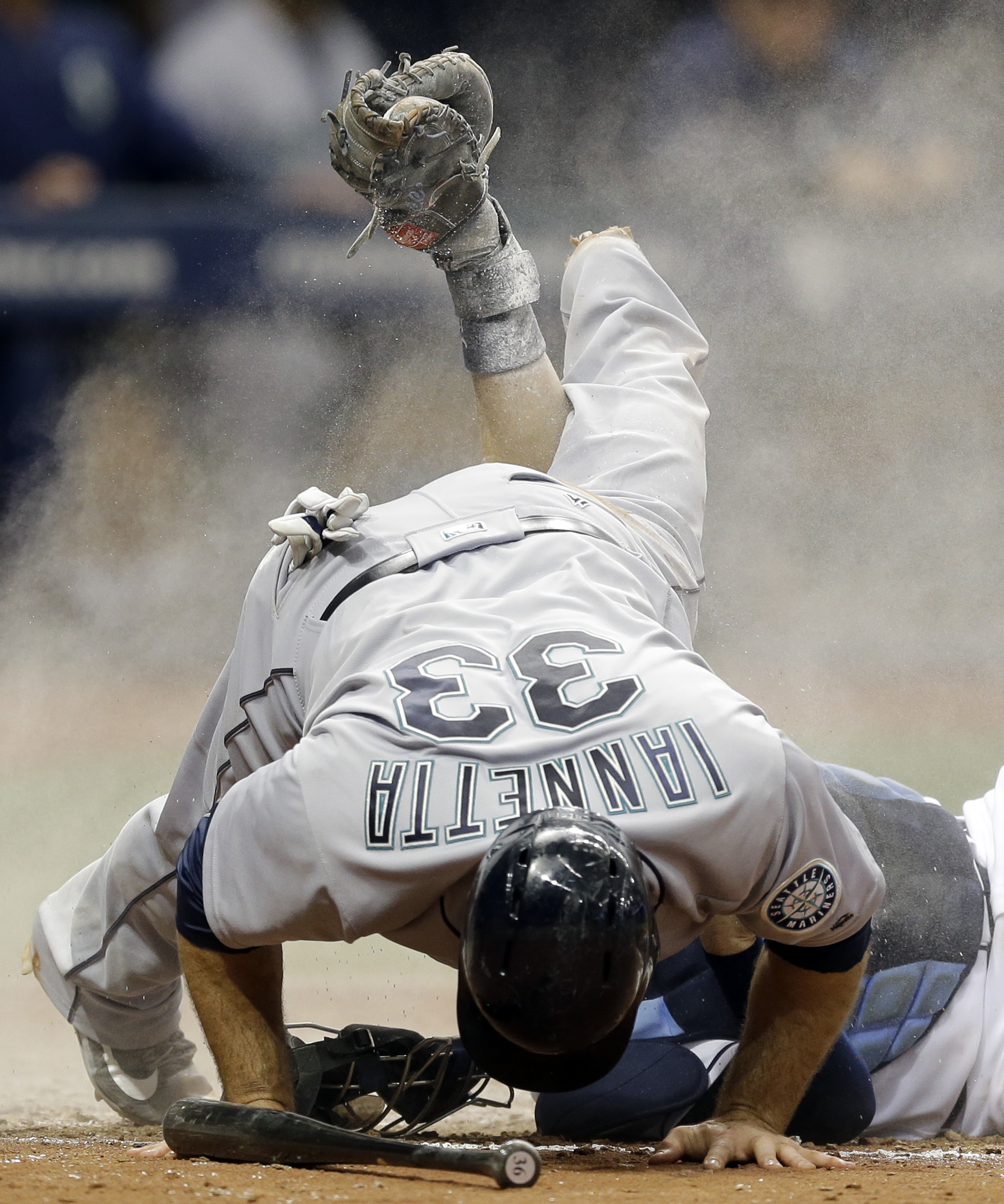 Seattle Mariners' Chris Iannetta knocks over Tampa Bay Rays catcher Curt Casali after being tagged out at home plate trying to score for third base on a fly out by Shawn O'Malley during the seventh inning of a baseball game Thursday, June 16, 2016, in St.