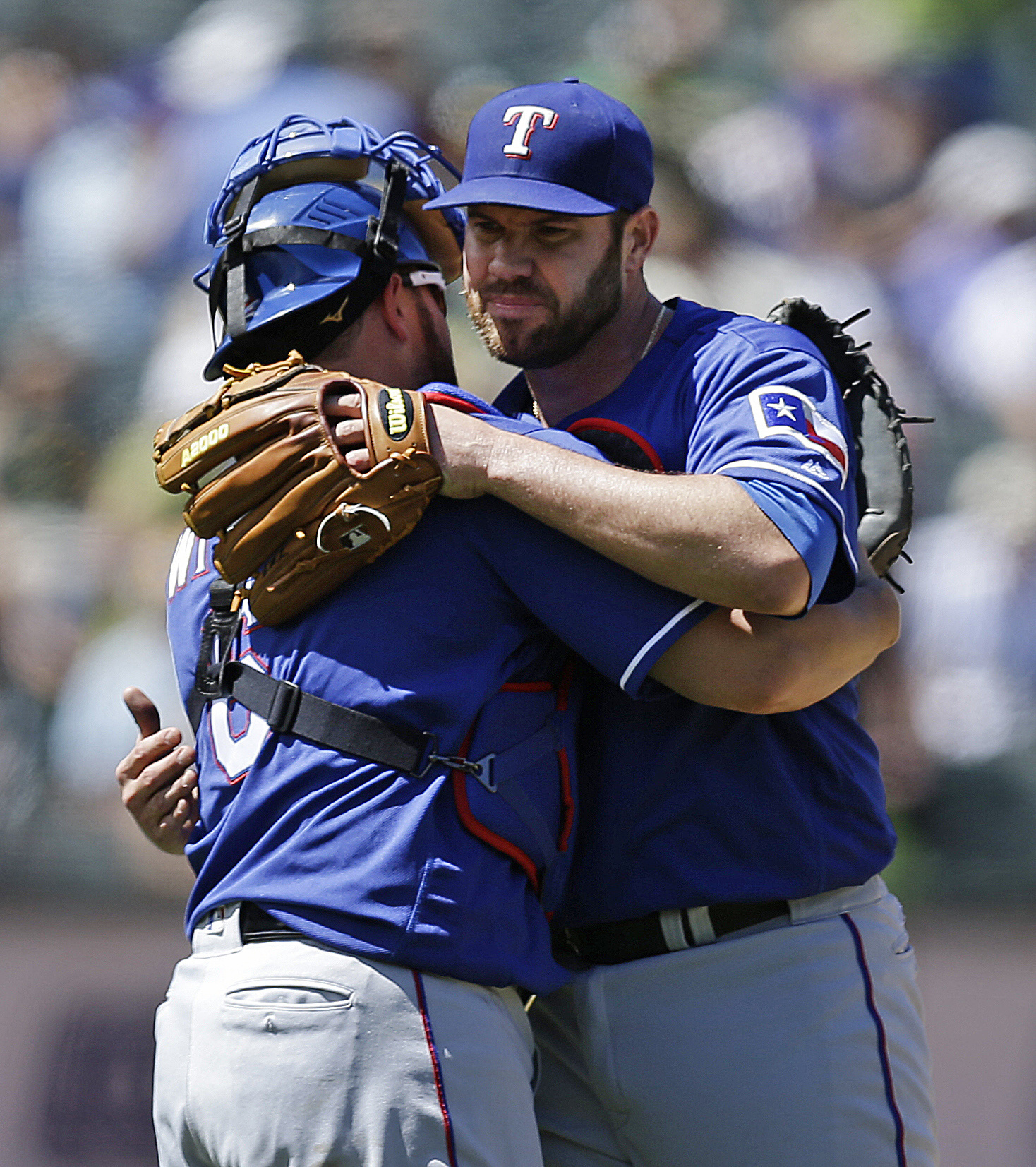 Texas Rangers pitcher Colby Lewis, right, and catcher Bobby Wilson embrace at the end of a baseball game against the Oakland Athletics, Thursday, June 16, 2016, in Oakland, Calif. (AP Photo/Ben Margot)