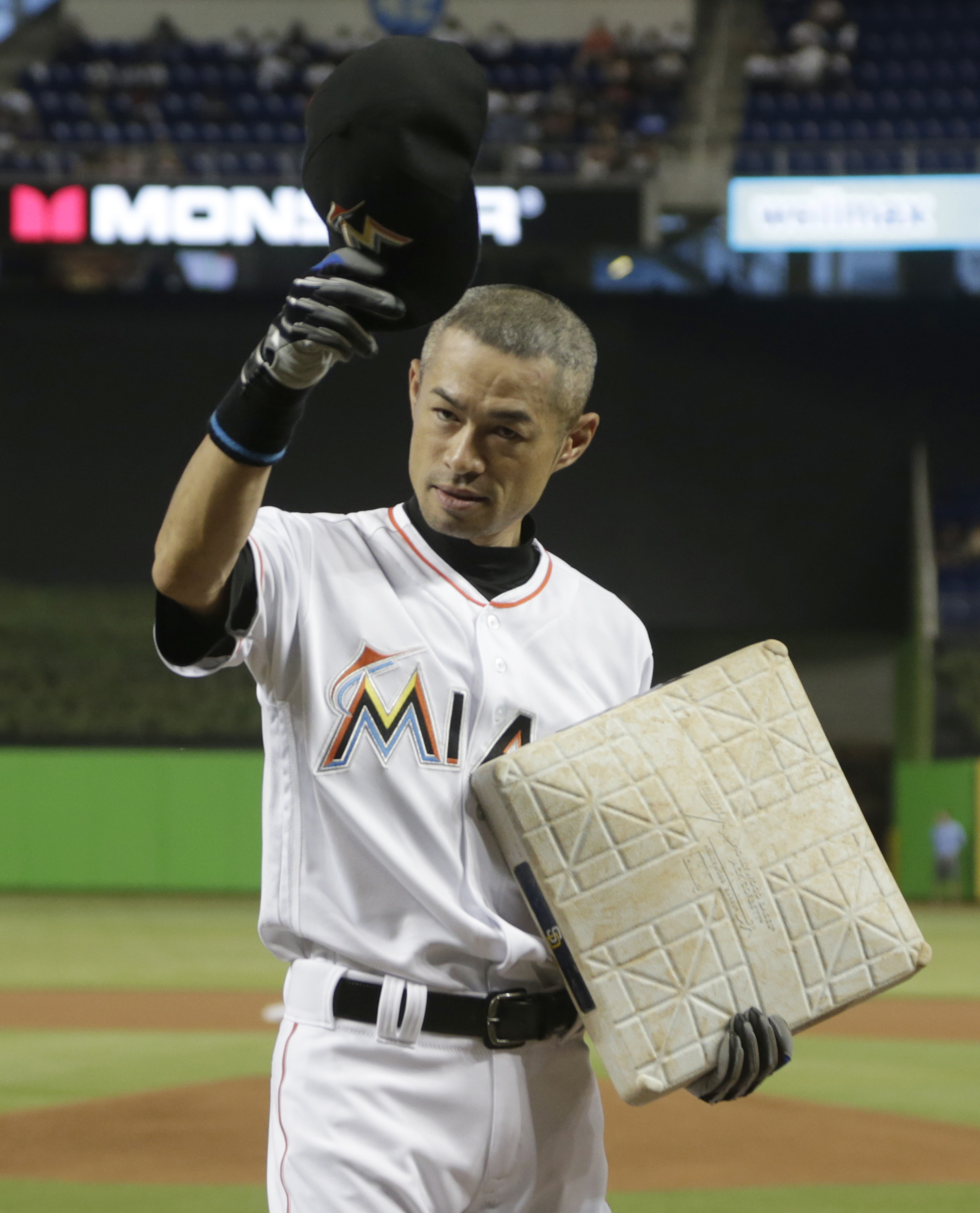 Miami Marlins' Ichiro Suzuki tips his cap after being presented with a base from the Marlins' game played against the San Diego Padres where Suzuki reached a career total of 4,257 hits in the Japanese and North American major leagues, before of a baseball