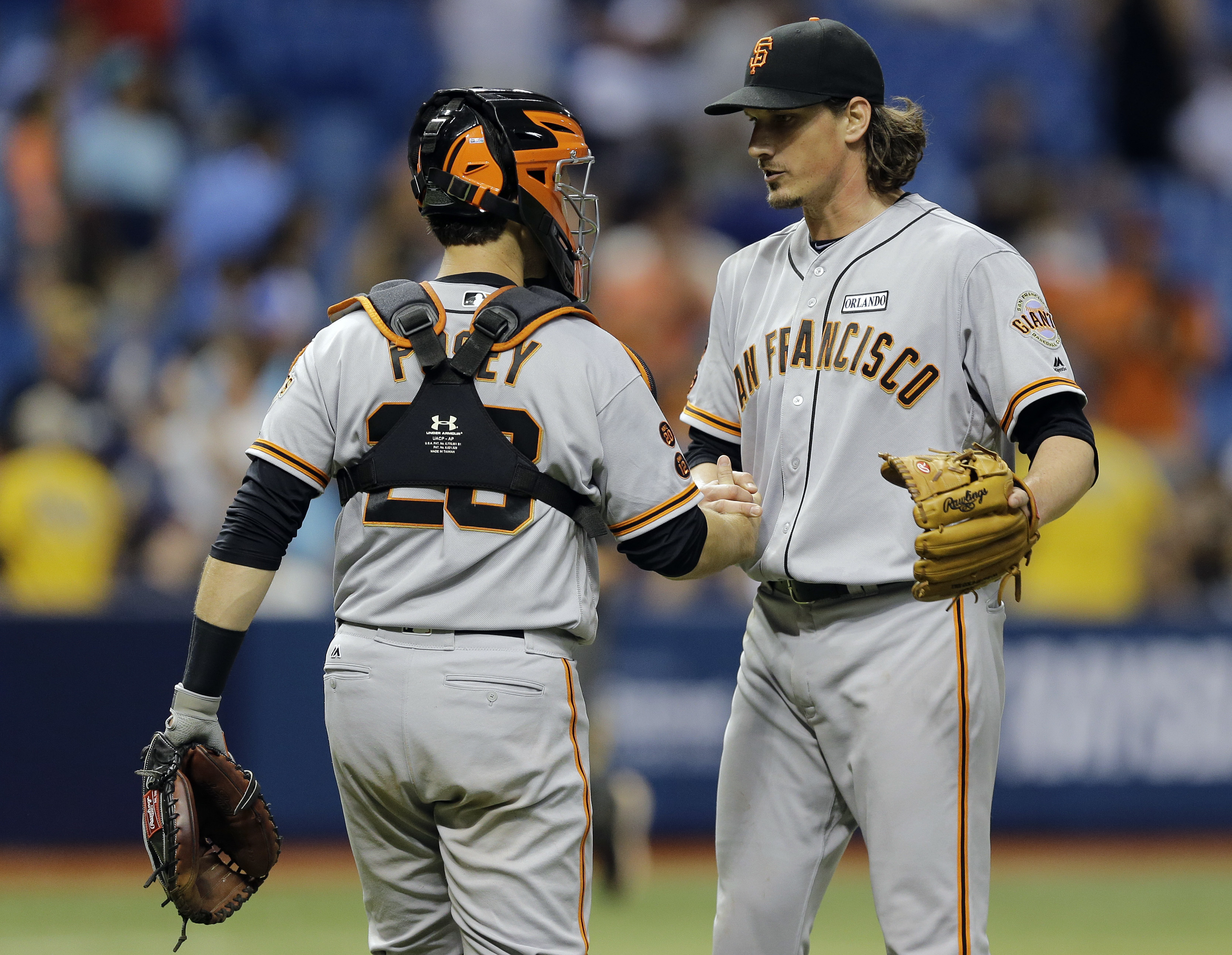 San Francisco Giants starting pitcher Jeff Samardzija, right, shakes hands with catcher Buster Posey after closing out the Tampa Bay Rays during the ninth inning of a baseball game Friday, June 17, 2016, in St. Petersburg, Fla. (AP Photo/Chris O'Meara)