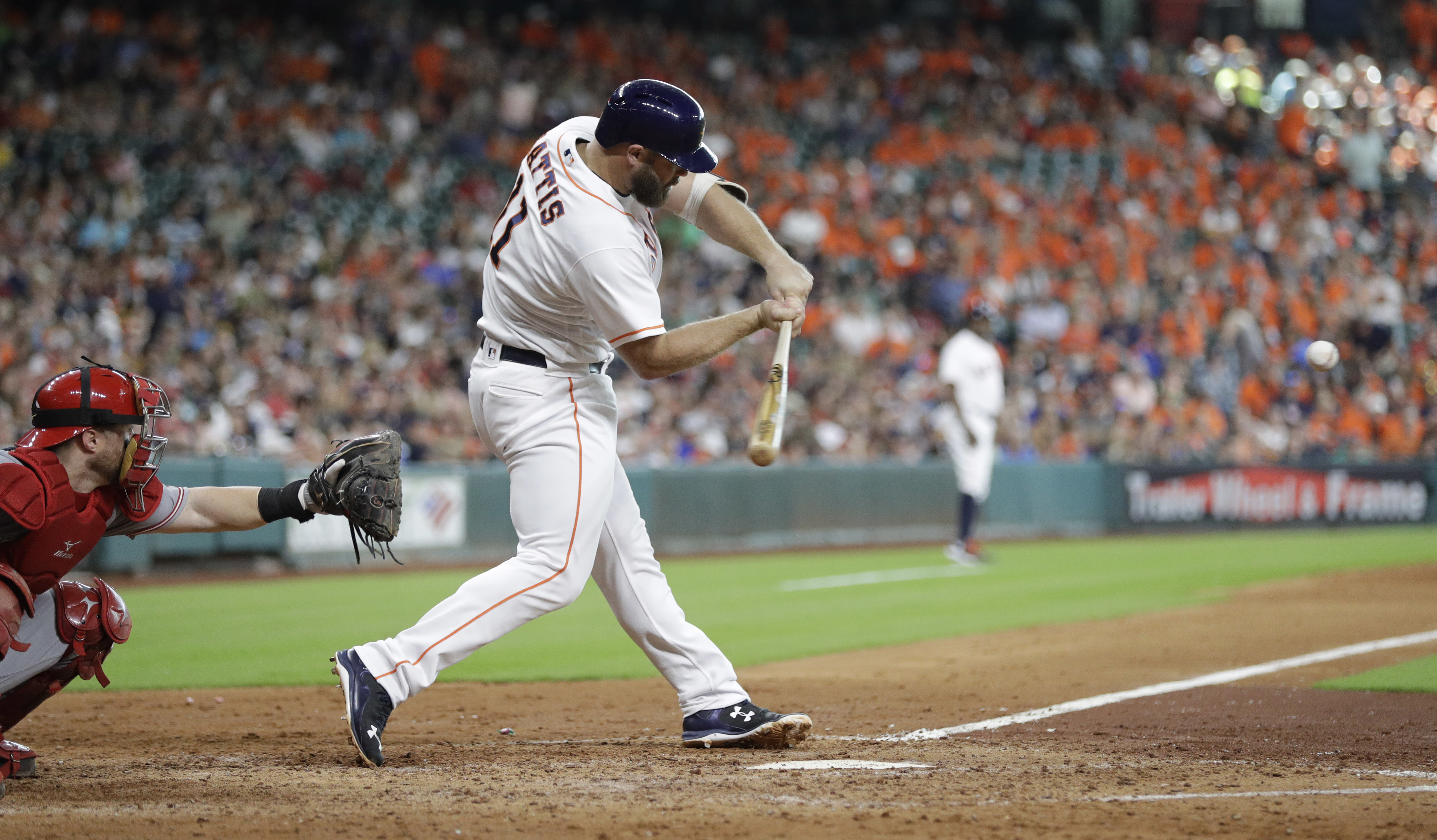 Houston Astros' Evan Gattis (11) swings to hit a two-run home run as Cincinnati Reds catcher Tucker Barnhart, left, reaches for the pitch during the seventh inning of a baseball game Saturday, June 18, 2016, in Houston. (AP Photo/David J. Phillip)