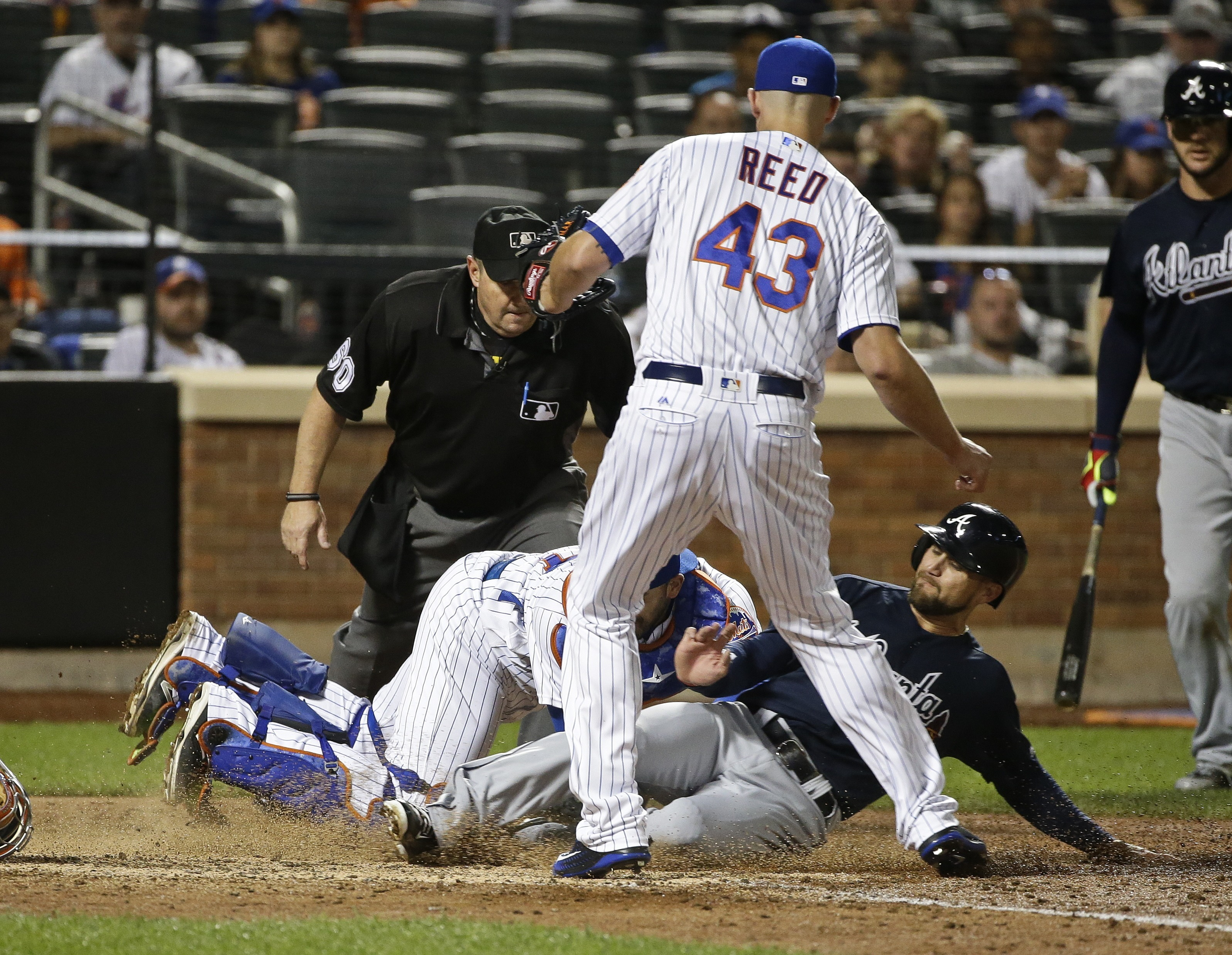 Atlanta Braves' Ender Inciarte, bottom right, steals home plate on a wild pitch by New York Mets relief pitcher Addison Reed (43) as catcher Rene Rivera, bottom left, attempts to tag him out during the eighth inning of a baseball game Saturday, June 18, 2
