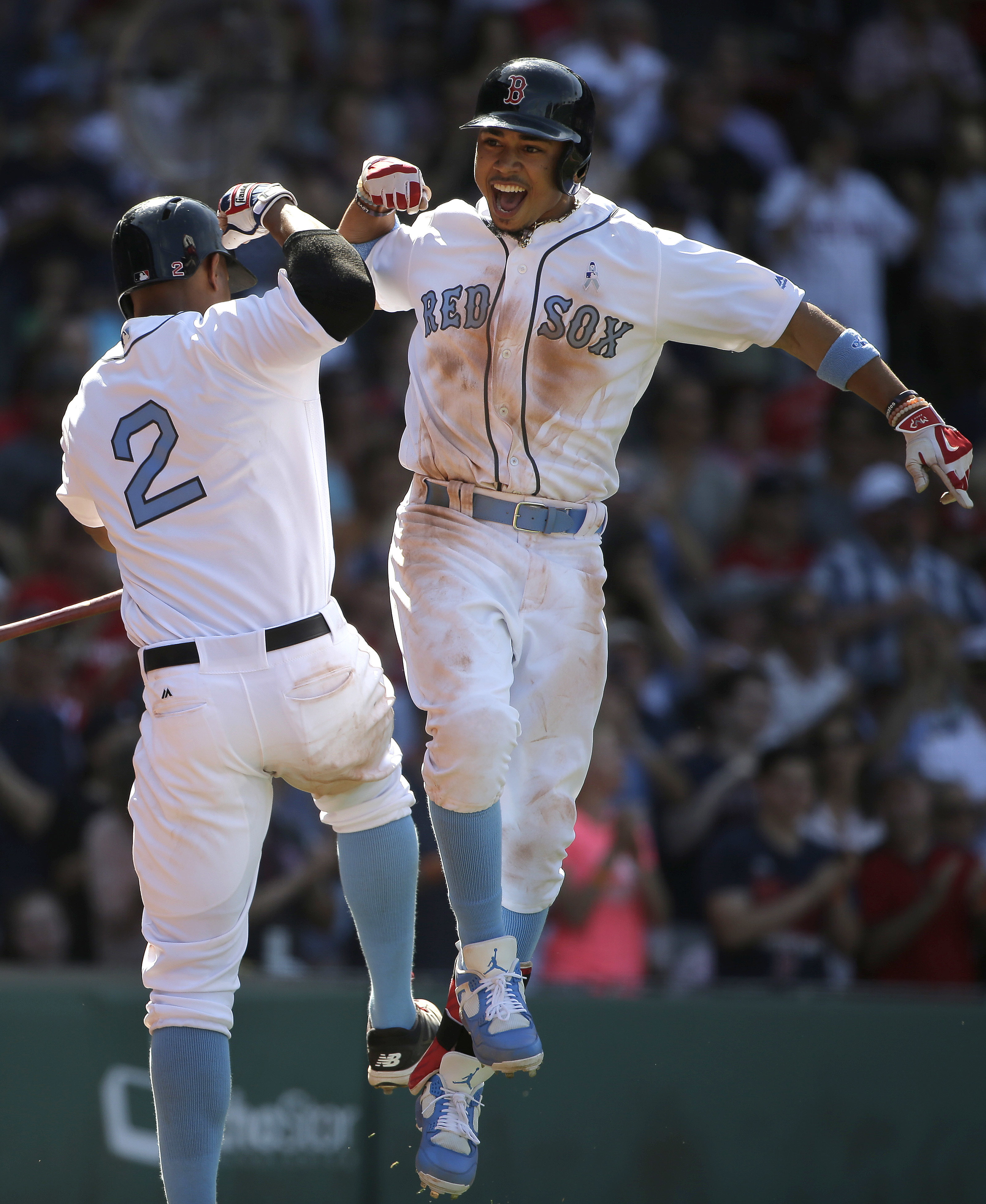 Boston Red Sox's Mookie Betts, right, celebrates with Xander Bogaerts as he arrives home after hitting a home run off a pitch by Seattle Mariners' Edwin Diaz in the seventh inning of a baseball game, Sunday, June 19, 2016, in Boston. (AP Photo/Steven Senn