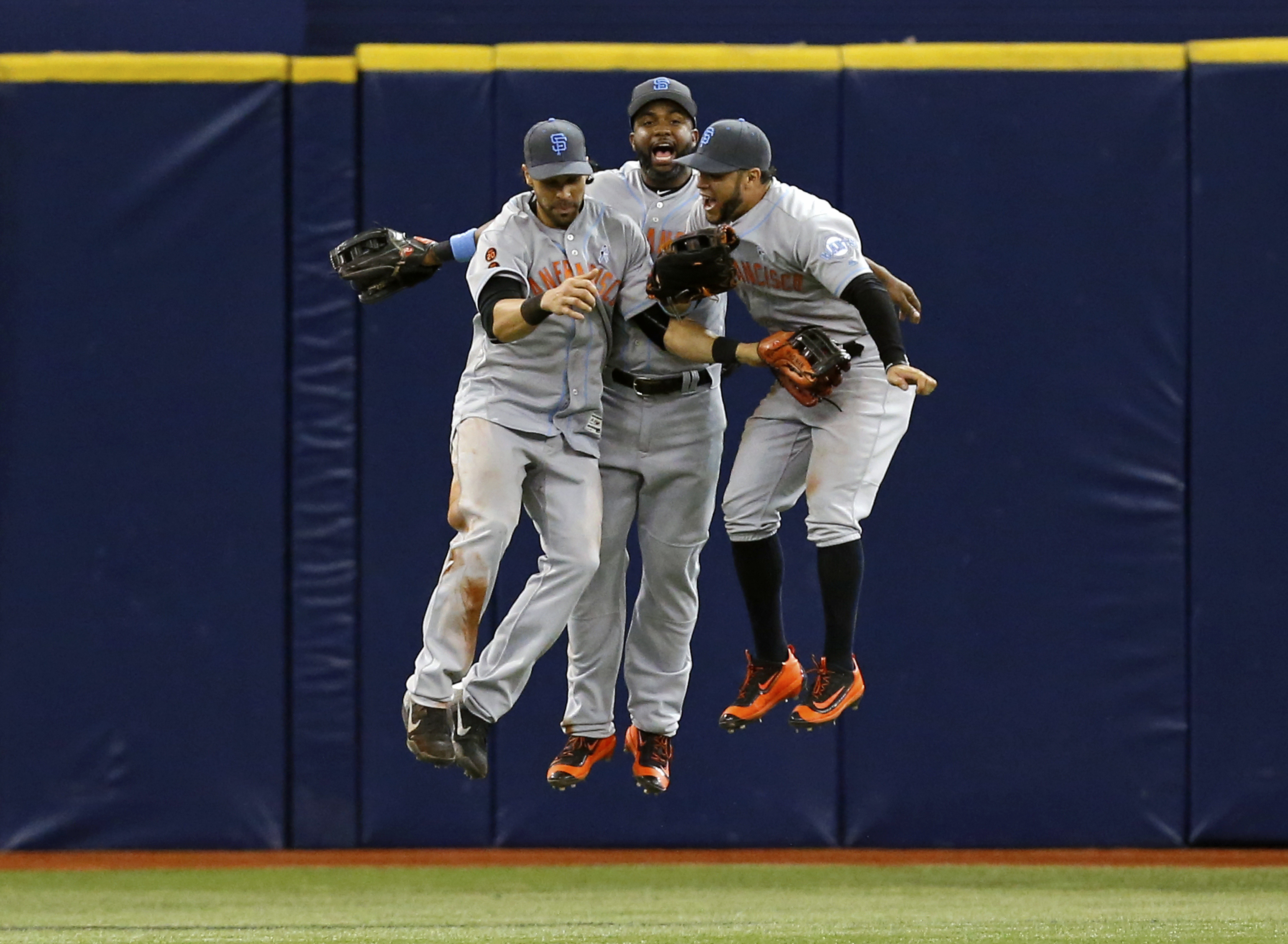 San Francisco Giants outfielders, from left, Angel Pagan, Denard Span, and Gregor Blanco celebrate at the end of a 5-1 win over the Tampa Bay Rays in a baseball game, Sunday, June 19, 2016, in St. Petersburg, Fla. (AP Photo/Mike Carlson)