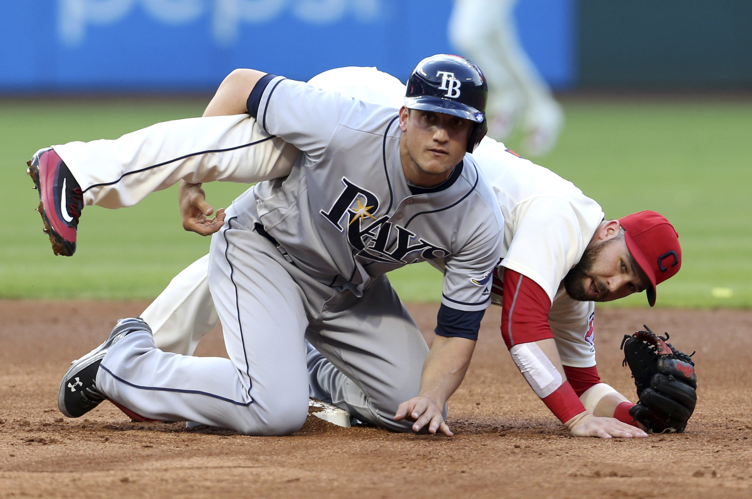 Cleveland Indians' Jason Kipnis, right, and Tampa Bay Rays' Mikie Mahtook watch Kipnis' throw to first for the out on Curt Casali to complete a double play during the second inning of a baseball game Monday, June 20, 2016, in Cleveland. (AP Photo/Ron Schw