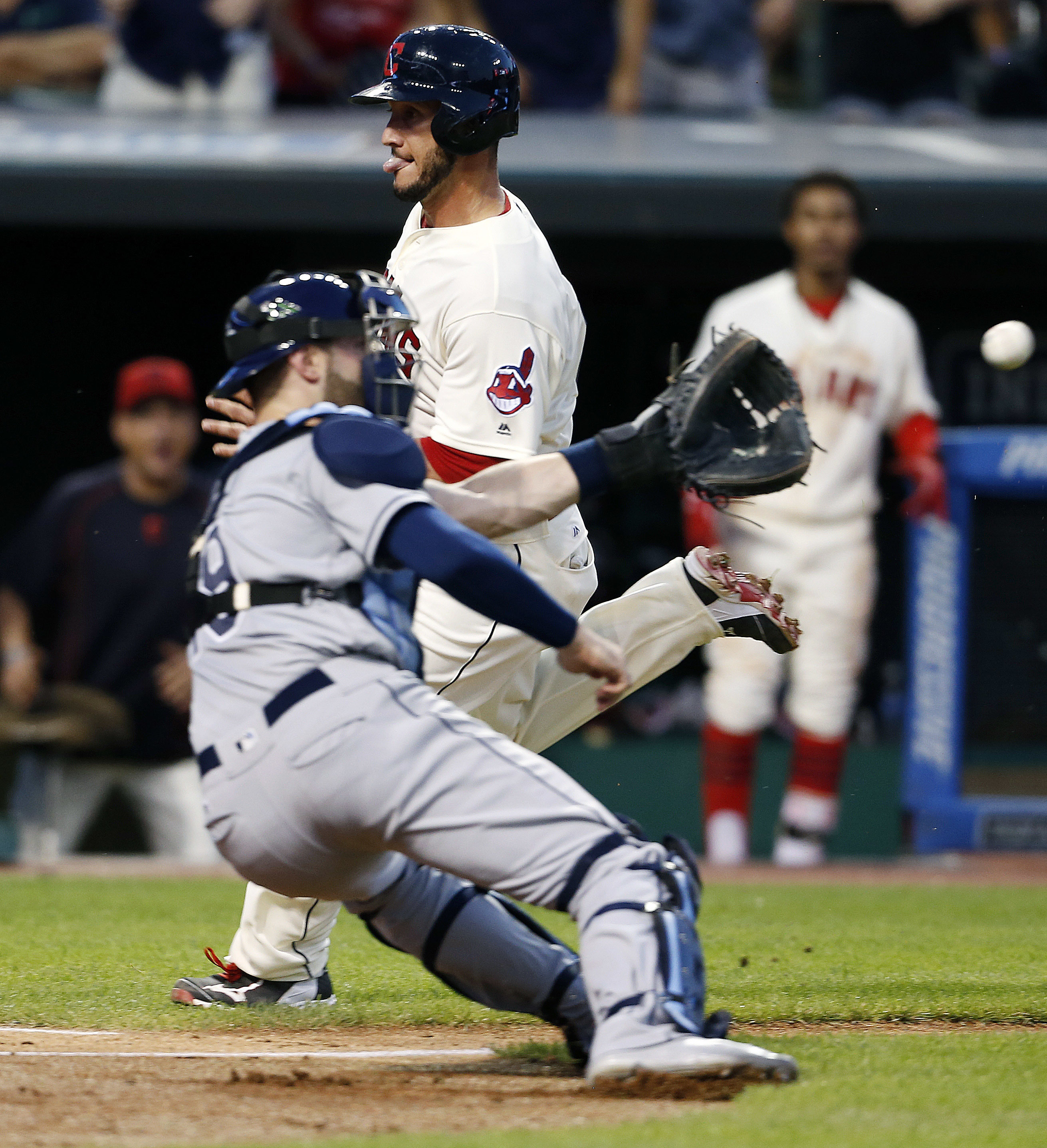Cleveland Indians' Yan Gomes scores past Tampa Bay Rays catcher Curt Casali (19) on a sacrifice fly by Rajai Davis during the seventh inning of a baseball game Monday, June 20, 2016, in Cleveland. (AP Photo/Ron Schwane)