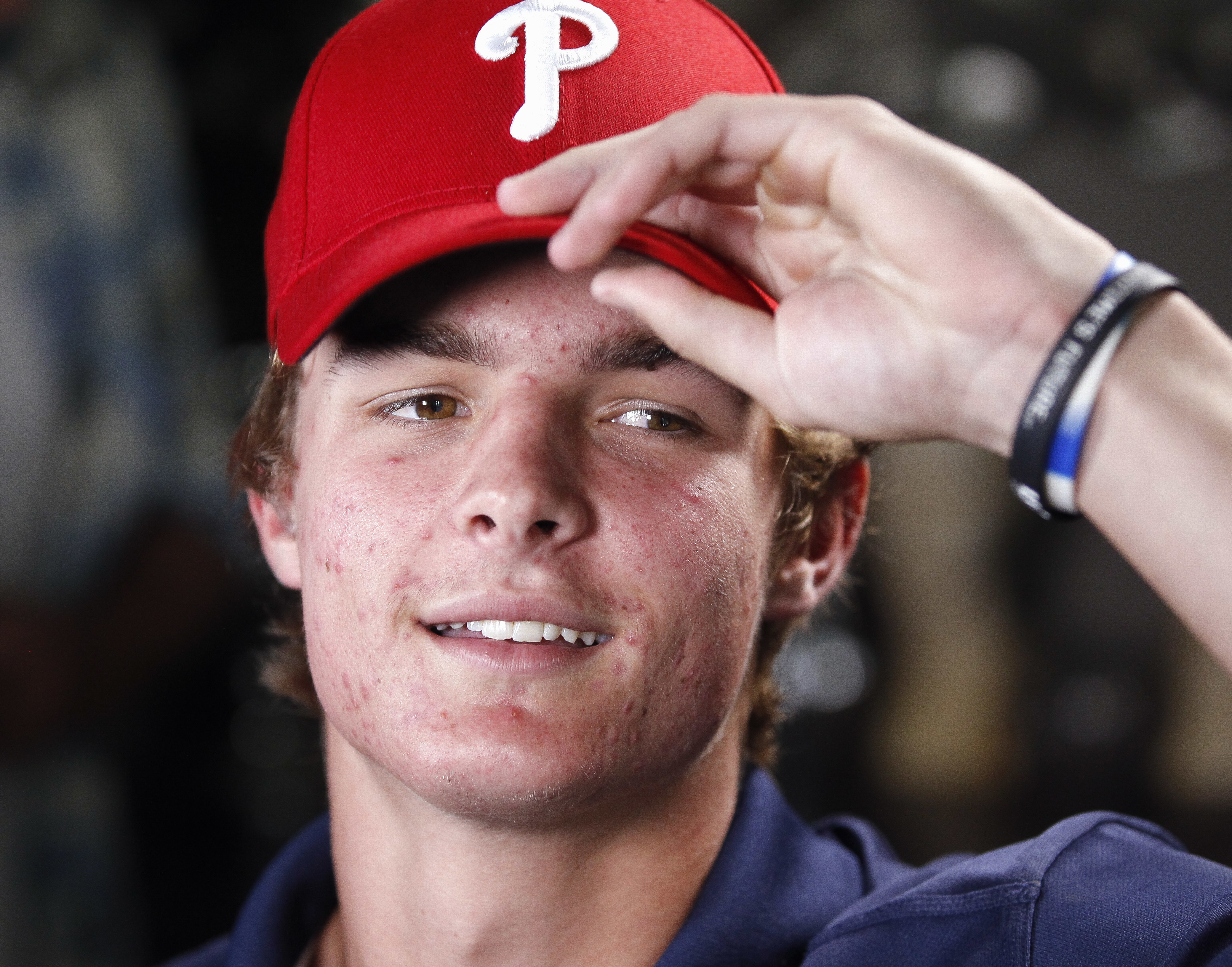 FILE - In this June 9, 2016, file photo, La Costa Canyon baseball player Mickey Moniak puts on a Philadelphia Phillies cap after the Phillies had chosen Moniak with the top pick in the Major League Baseball draft, at Moniak's aunt's house in Carlsbad, Cal