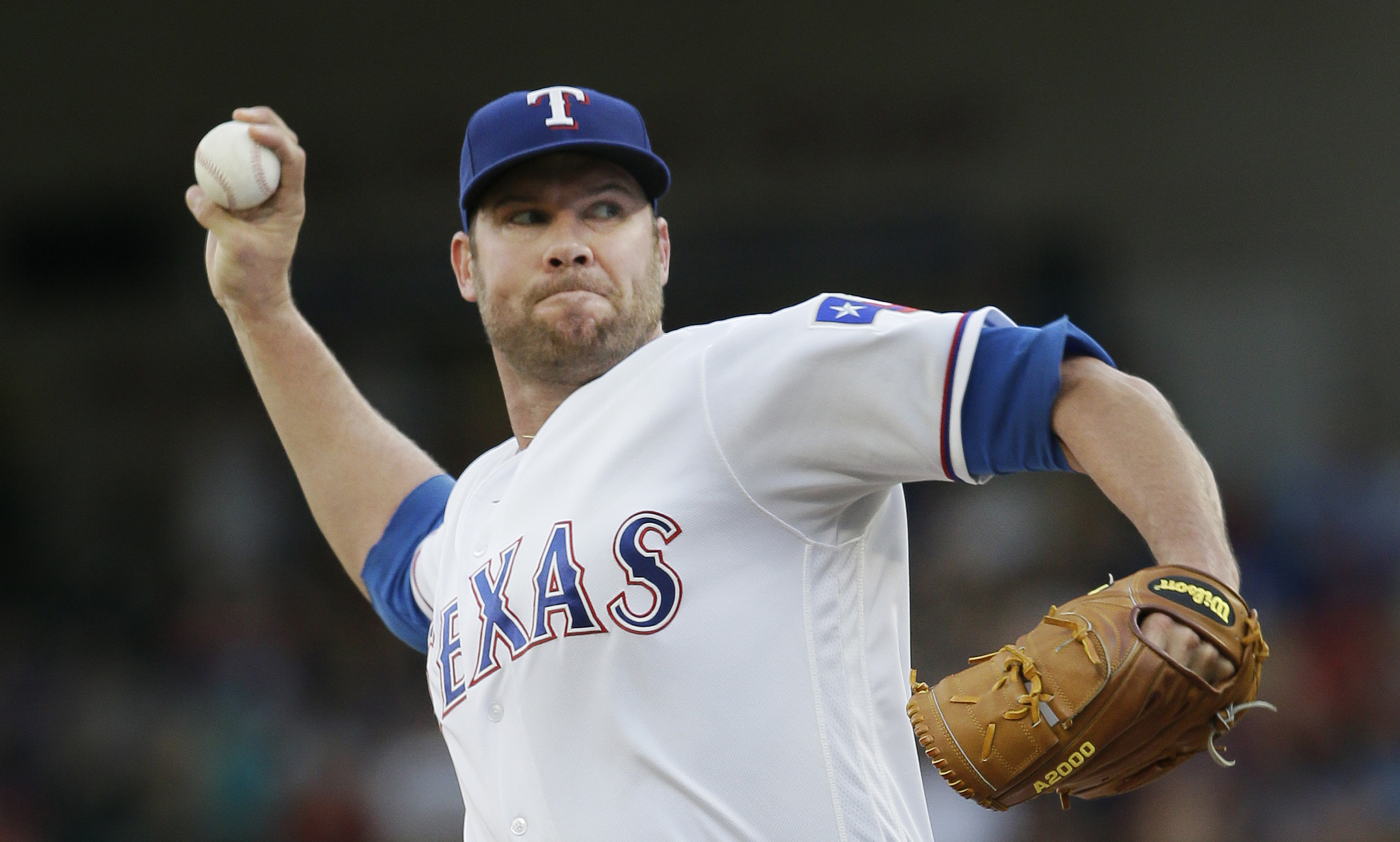Texas Rangers starting pitcher Colby Lewis throws during the first inning of a baseball game against the Cincinnati Reds in Arlington, Texas, Tuesday, June 21, 2016. (AP Photo/LM Otero)