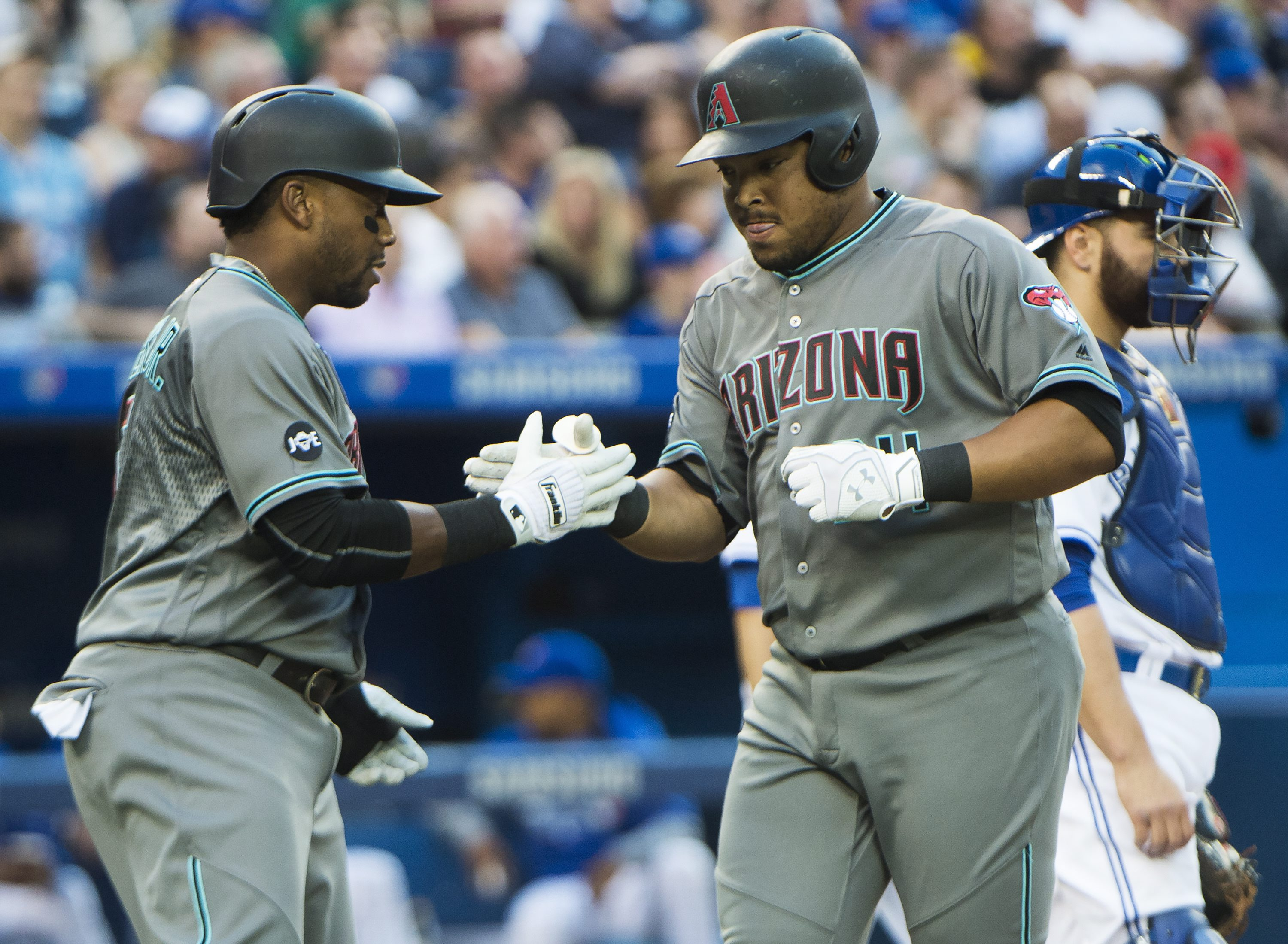 Arizona Diamondbacks left fielder Yasmany Tomas, right, celebrates his two run home run against the Toronto Blue Jays with teammate Rickie Weeks during the fourth inning of a baseball game, Tuesday, June 21, 2016, in Toronto. (Nathan Denette/The Canadian