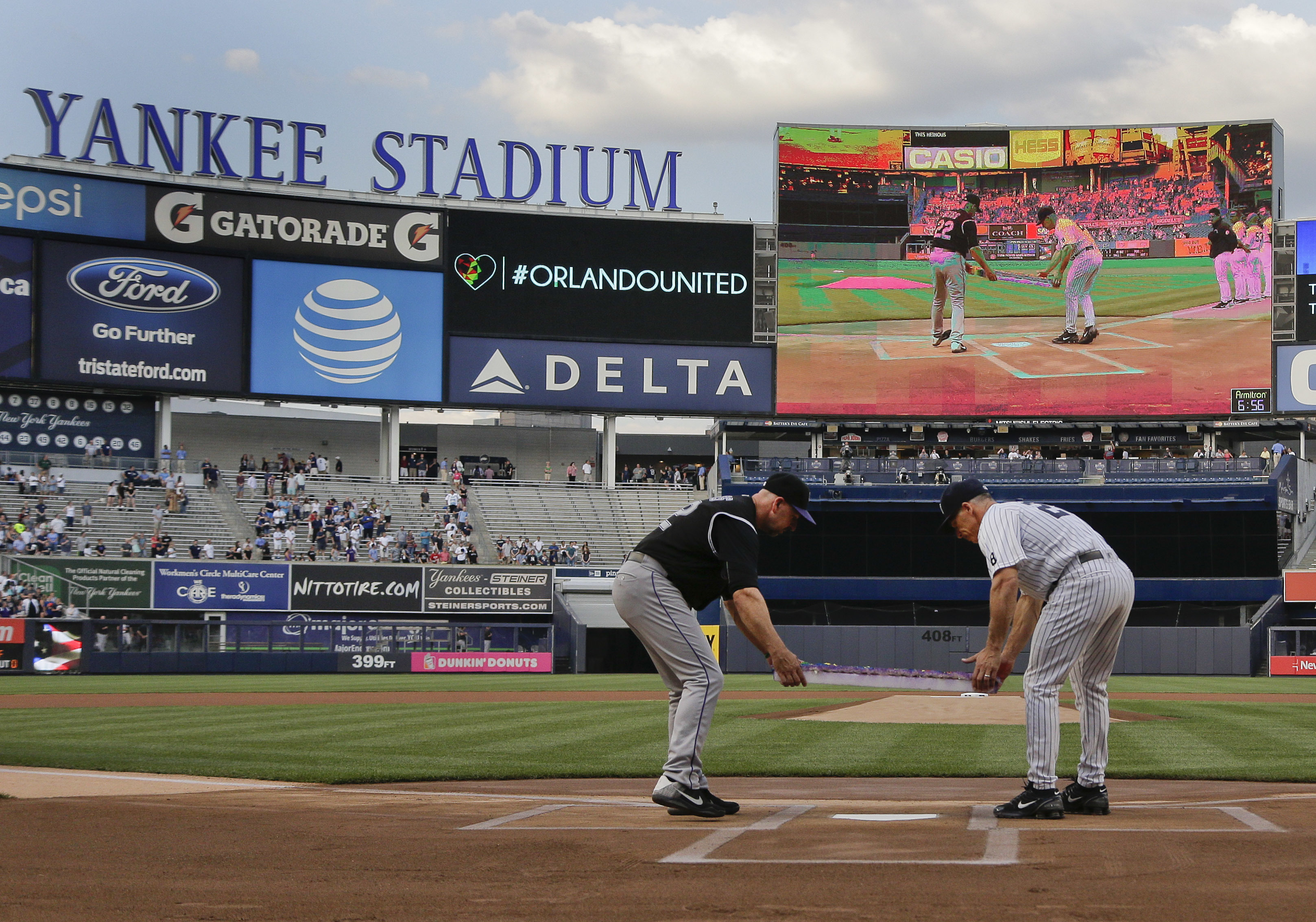 Colorado Rockies manager Walt Weiss, left, and New York Yankees manager Joe Girardi lay a rainbow-colored wreath across home plate during a ceremony remembering the victims of the Orlando shootings, before a baseball game Tuesday, June 21, 2016, in New Yo