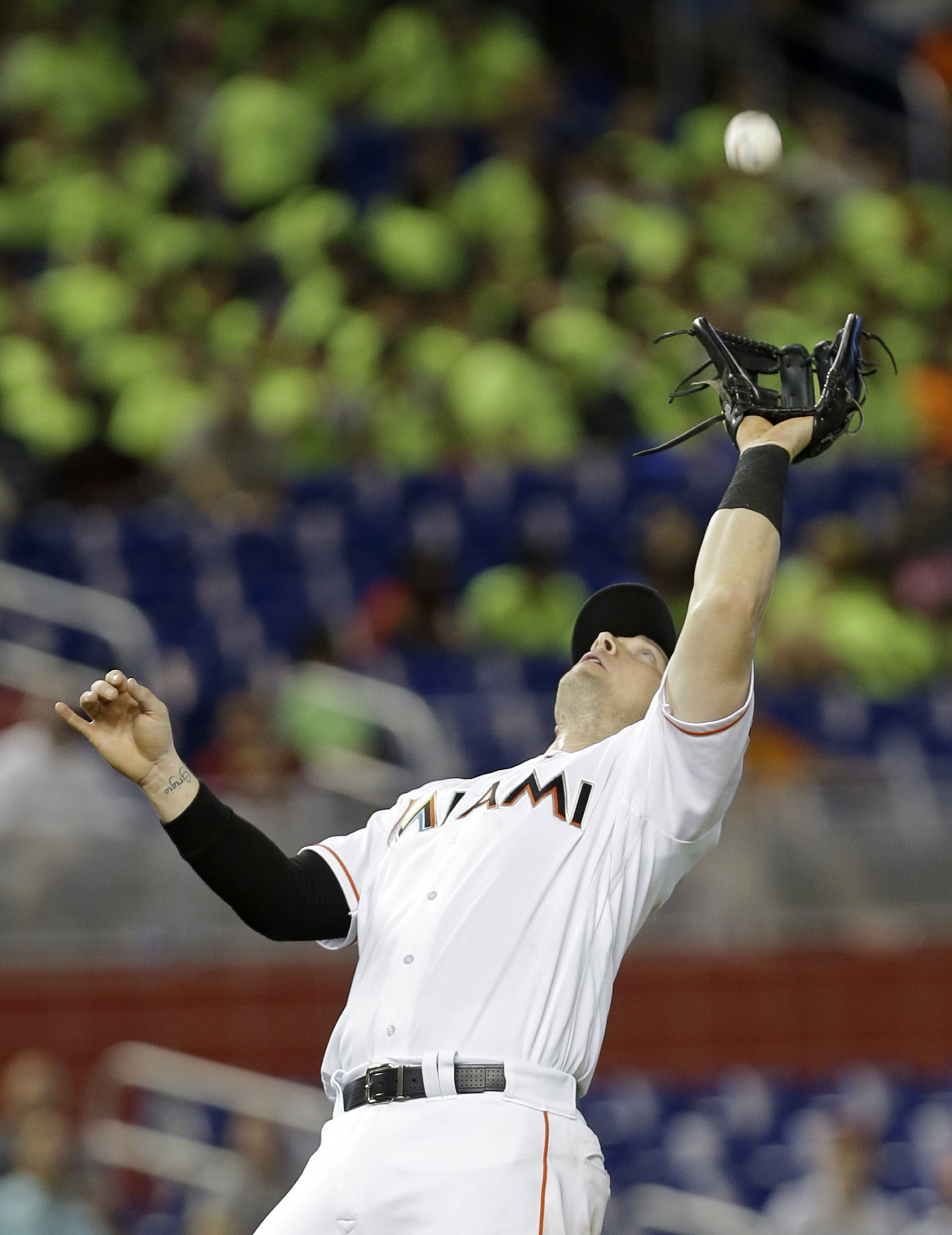 Miami Marlins second baseman Derek Dietrich catches a pop up fly ball by Atlanta Braves' Chase d'Arnaud in the second inning of a baseball game, Wednesday, June 22, 2016, in Miami. (AP Photo/Alan Diaz)