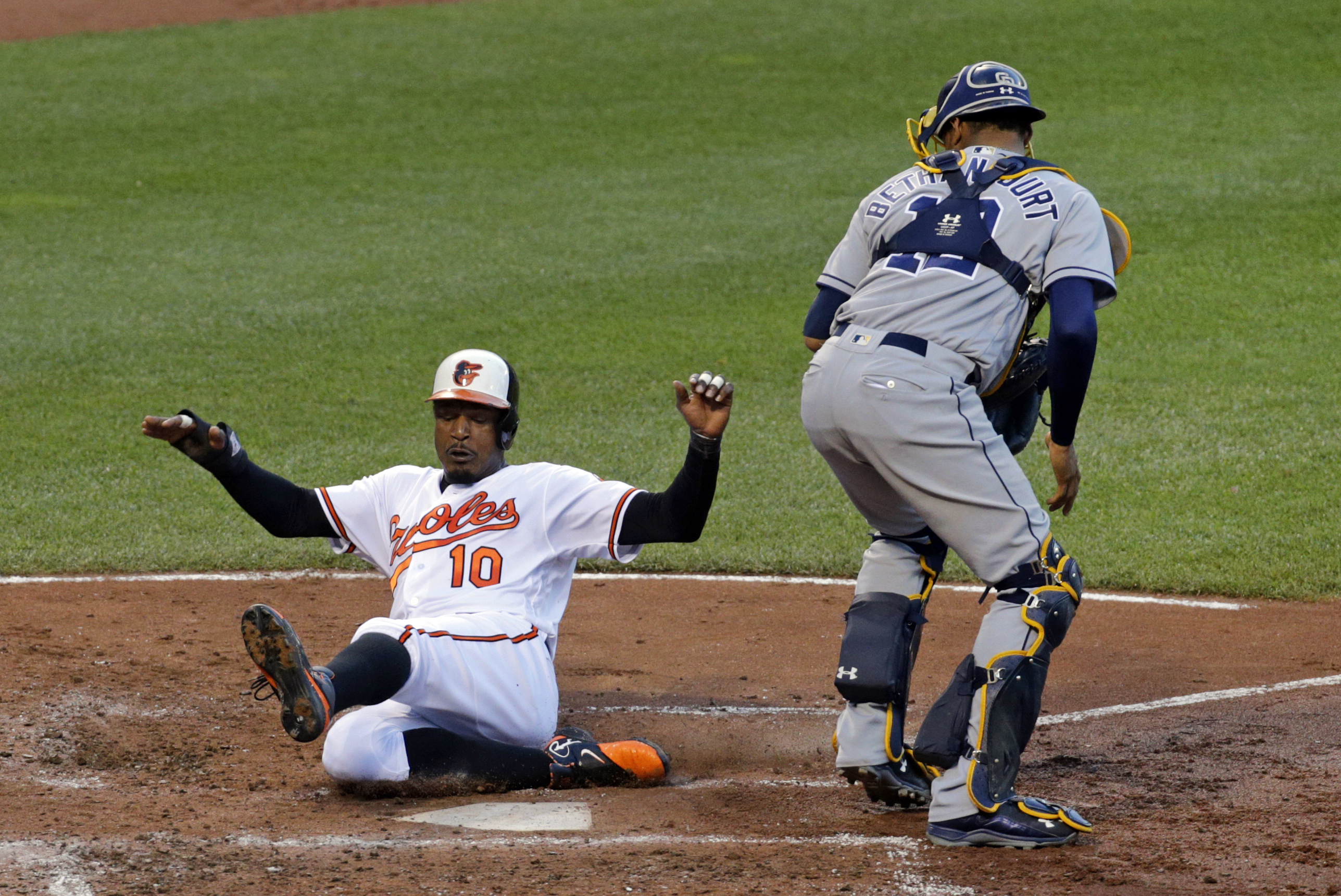Baltimore Orioles' Adam Jones, left, scores in front of San Diego Padres catcher Christian Bethancourt on a Jonathan Schoop double in the third inning of an interleague baseball game in Baltimore, Wednesday, June 22, 2016. (AP Photo/Patrick Semansky)