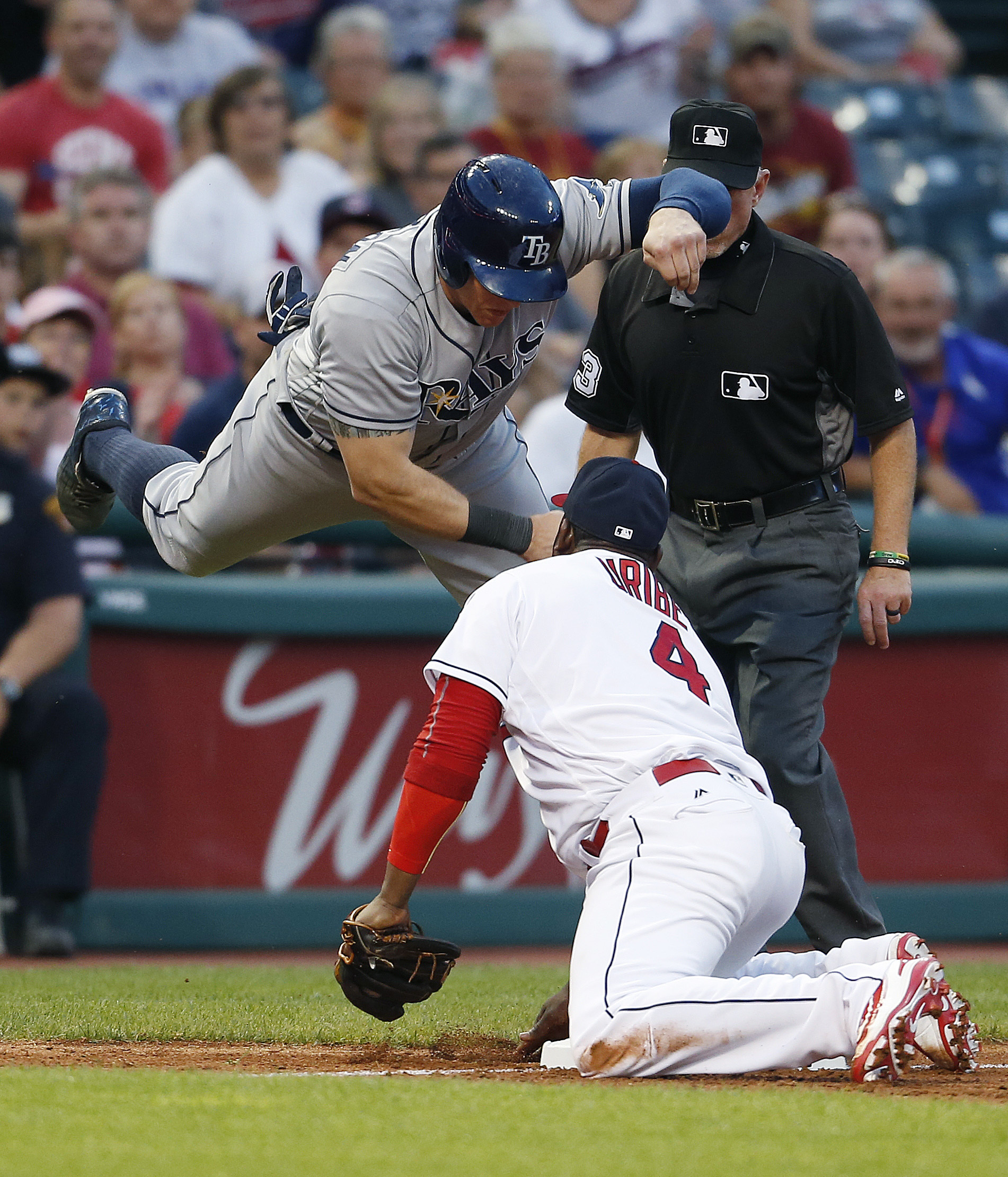 Cleveland Indians' Juan Uribe (4) tags out Tampa Bay Rays' Logan Morrison (7) at third base after Morrison over ran the base as third base umpire Lance Barksdale looks on during the seventh inning of a baseball game, Wednesday, June 22, 2016, in Cleveland