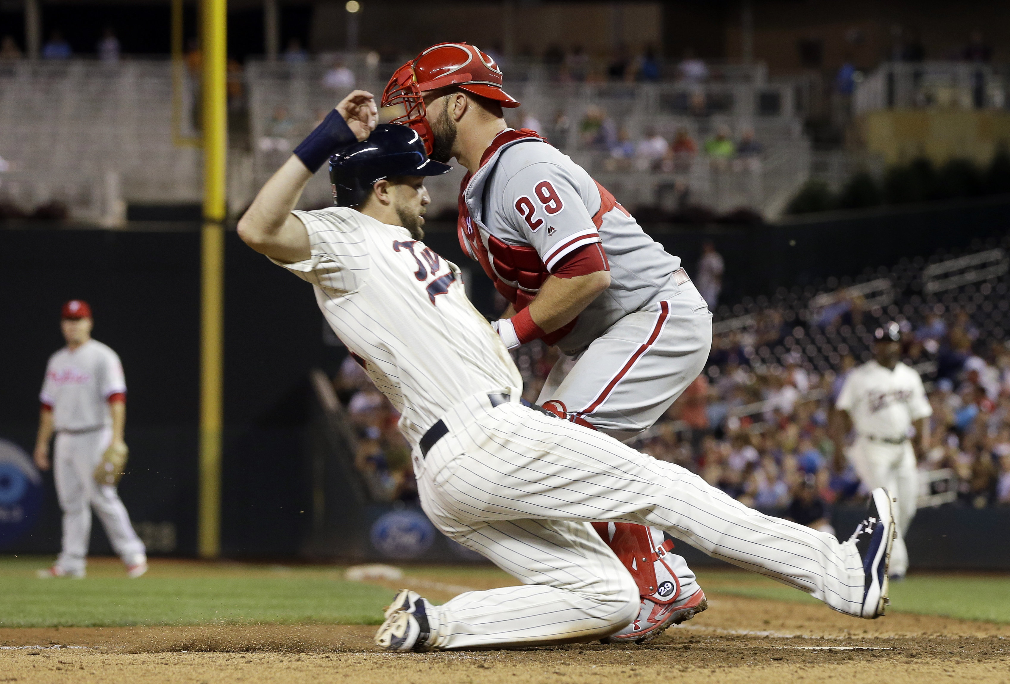 Minnesota Twins' Trevor Plouffe slides past Philadelphia Phillies catcher Cameron Rupp to score on a sacrifice fly by Max Kepler during the seventh inning of a baseball game Wednesday, June 22, 2016, in Minneapolis. The Twins won 6-5. (AP Photo/Jim Mone)