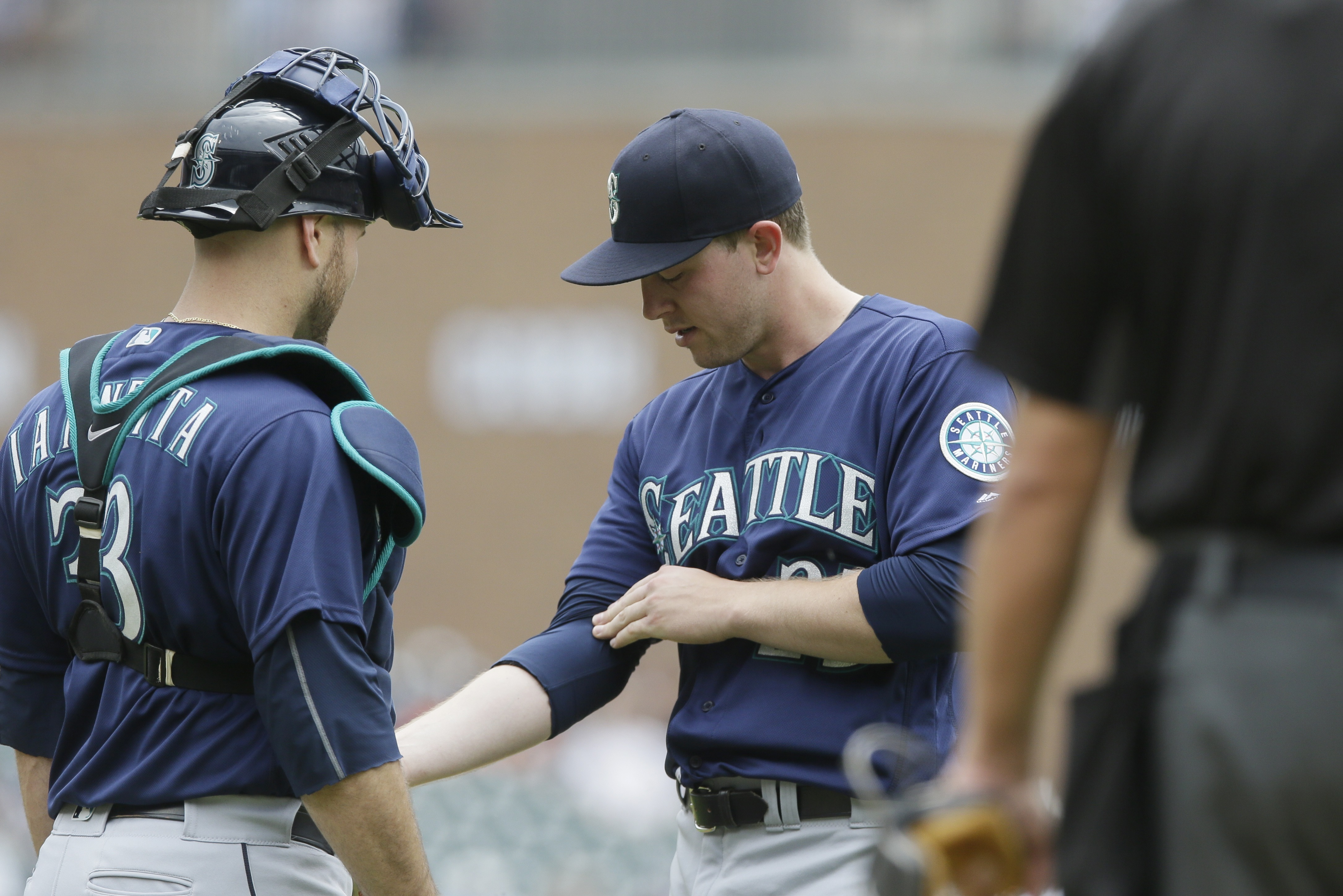 Seattle Mariners starting pitcher Adrian Sampson points to his right forearm as he talks with catcher Chris Iannetta before the first inning of a baseball game against the Detroit Tigers, Thursday, June 23, 2016 in Detroit. Sampson was replaced with pitch
